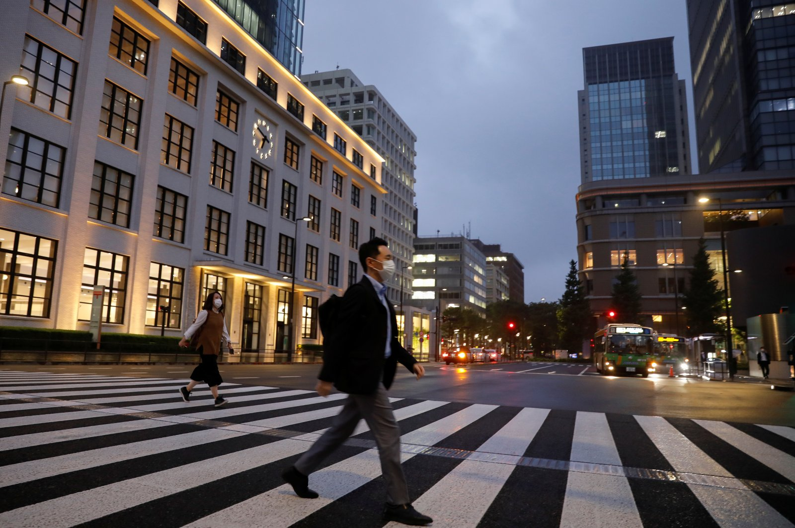 A pedestrian wearing a protective face mask crosses a street, amid the coronavirus outbreak, in the business district in Tokyo, Japan, May 21, 2020. (Reuters Photo)