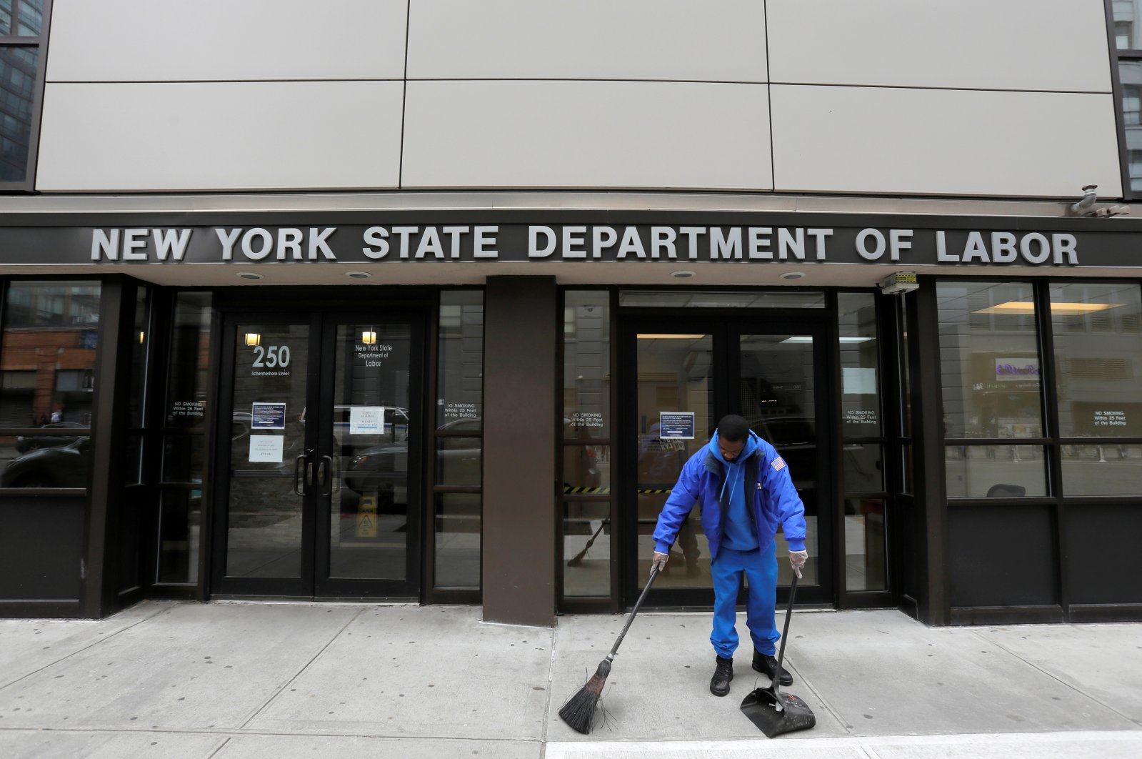 A person sweeps outside the entrance of the New York State Department of Labor offices, which is closed to the public due to the coronavirus outbreak, in the Brooklyn borough of New York City, U.S., March 20, 2020. (Reuters Photo)