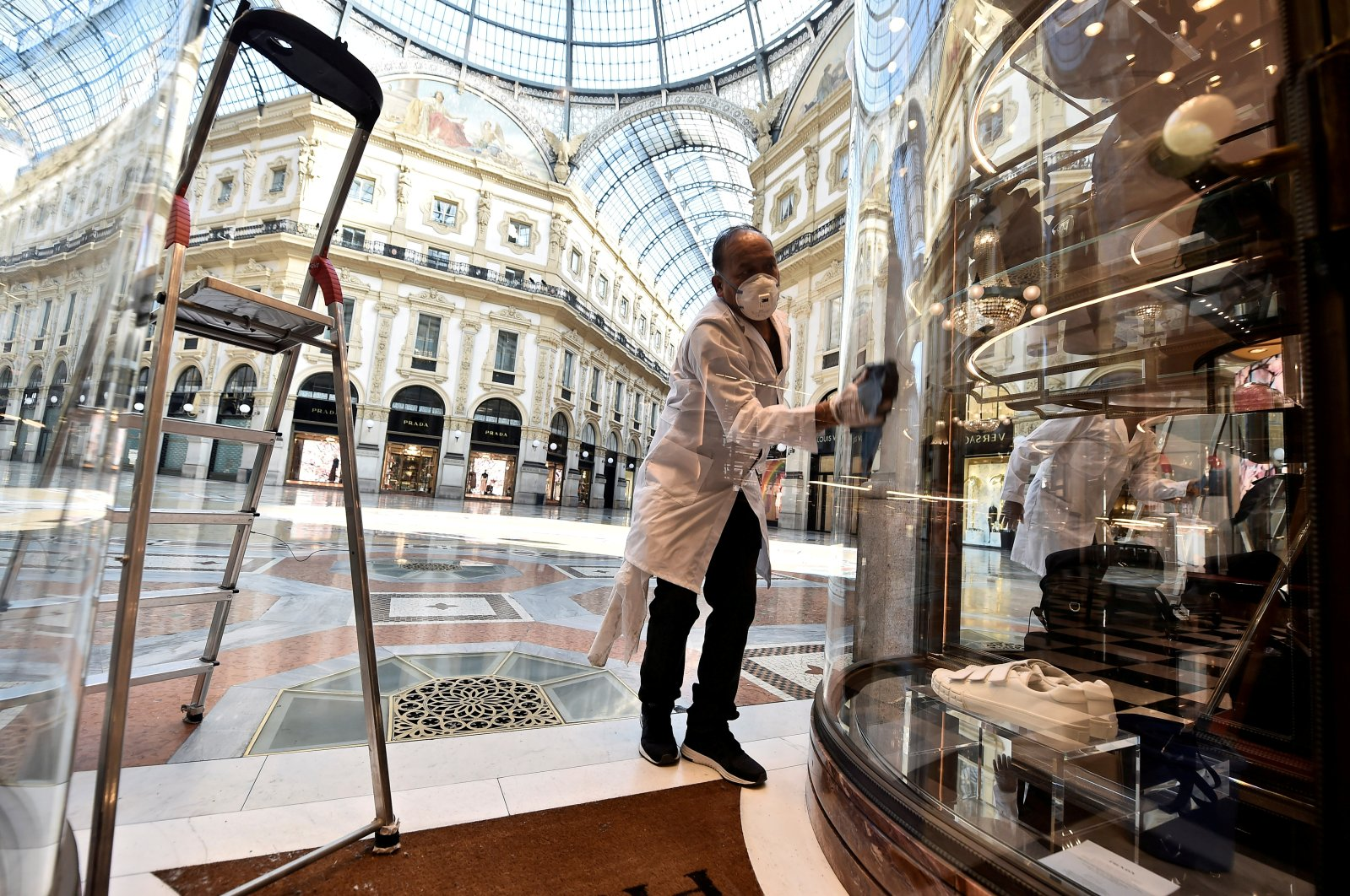 A worker prepares a store on the reopening day at Galleria Vittorio Emanuele II, as Italy eases some of the lockdown measures put in place during the coronavirus outbreak, in Milan, Italy, May 18, 2020. (Reuters Photo)