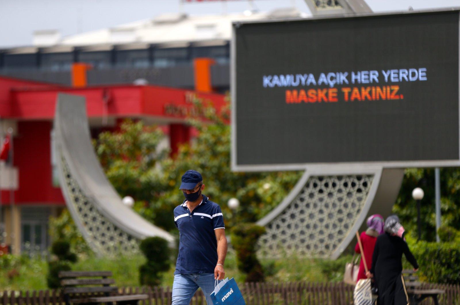 """A man wearing a mask walks past a billboard reading, """"Wear a mask in every public place,"""" in Düzce, Turkey, May 21, 2020. (AA Photo)"""
