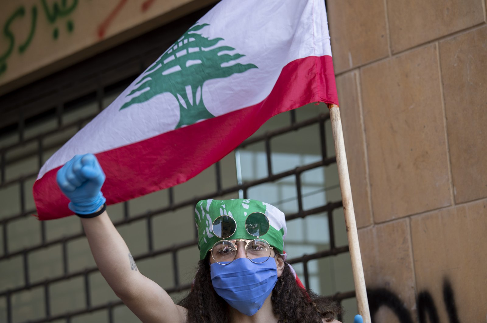 An anti-government protester shouts slogans, while wearing a mask to help curb the spread of the coronavirus, during ongoing protests in front of the Ministry of Economy, in downtown Beirut, Lebanon, May 18, 2020. (AP Photo)