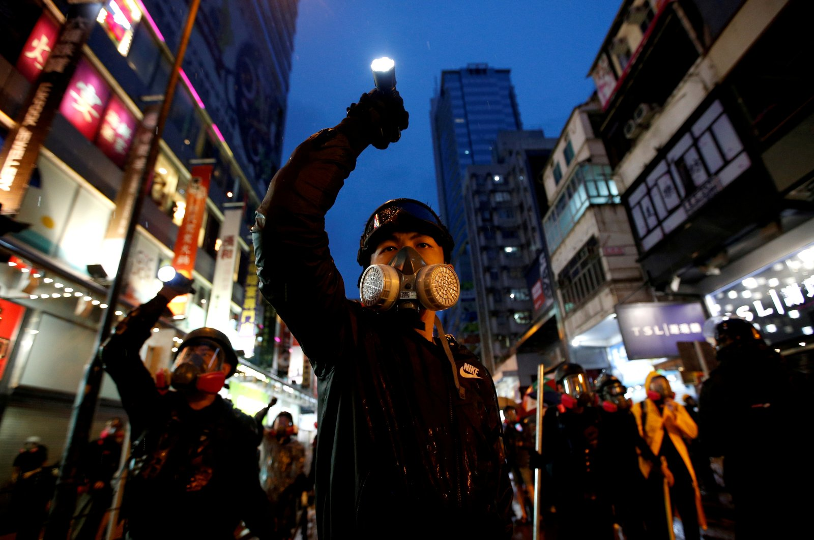 Demonstrators protesting the proposed extradition bill aim their flashlights toward riot police as they are chased through the streets of Hong Kong, China, Aug. 25, 2019. (Reuters Photo)