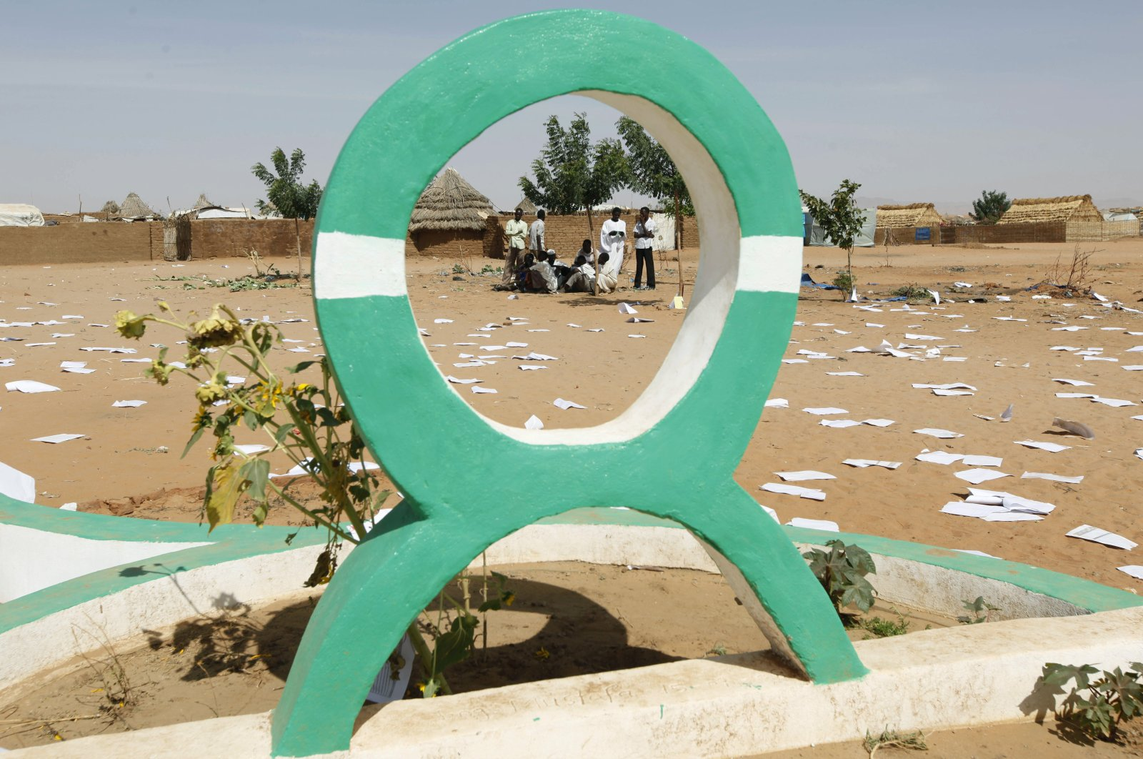 Sudanese refugees gather behind the Oxfam logo at al-Salam refugee camp, outside the Darfur town of al-Fasher, March 21, 2009. (AP Photo)