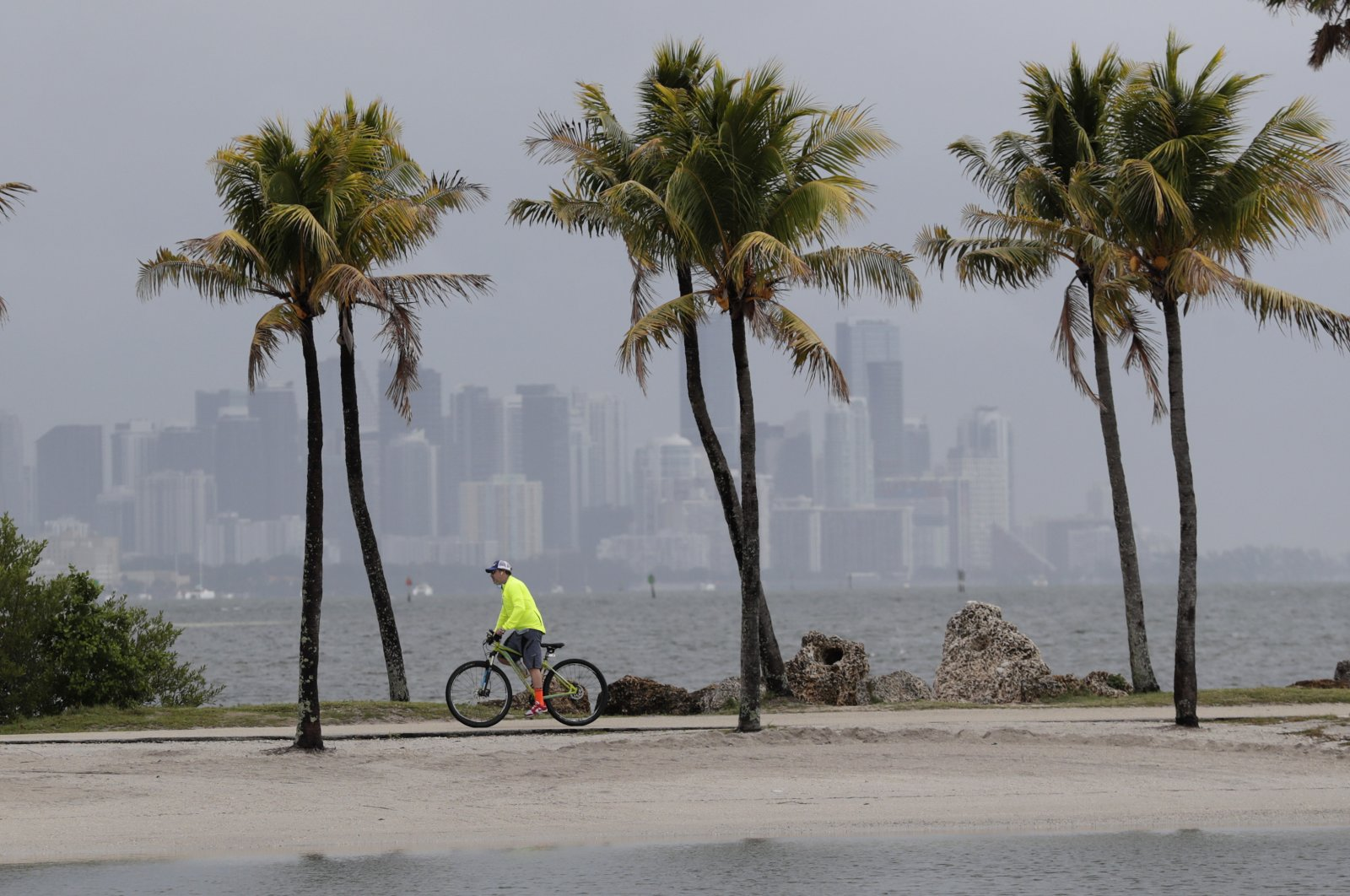 The Miami skyline is shrouded in clouds as a cyclist rides along Biscayne Bay at Matheson Hammock Park, Miami, May, 15, 2020. (AP Photo)