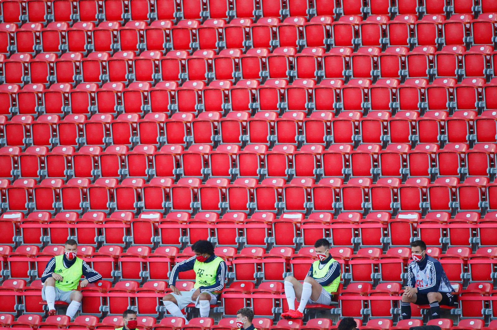 Bayern Munich substitutes wearing protective face masks maintain social distance in the stands during a Bundesliga football match against Union Berlin in Berlin, Germany, May 17, 2020. (AFP Photo)