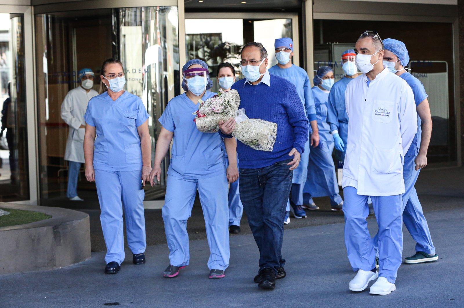 Hospital staff cheer as pulmonologist professor Bülent Tutluoğlu leaves a hospital following his COVID-19 treatment, Istanbul, Turkey, April 14, 2020. (AA Photo)