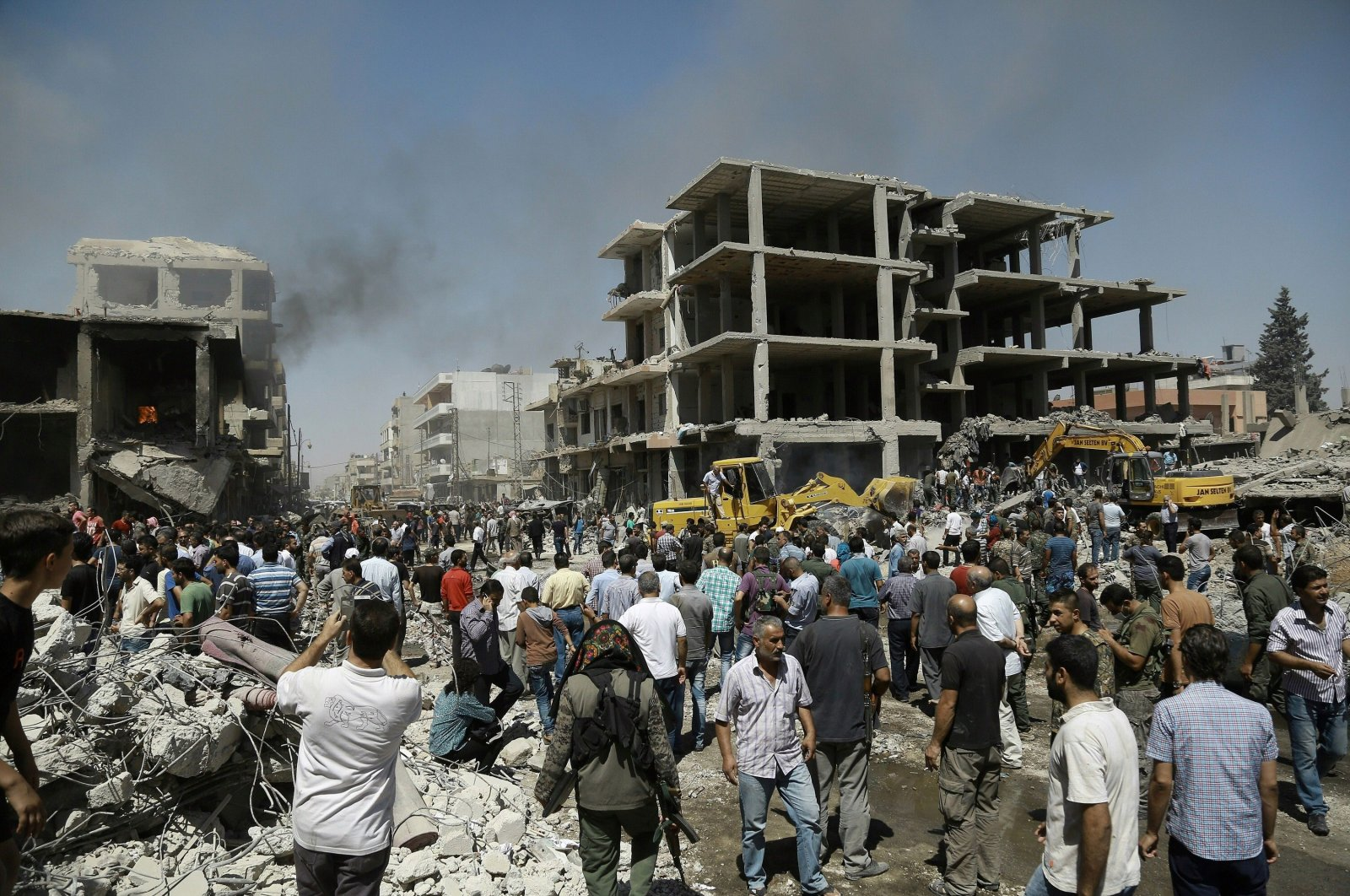 Syrians gather at the site of a YPG bomb attack in Syria's northeastern city of Qamishli on July 27, 2016 (AFP Photo)