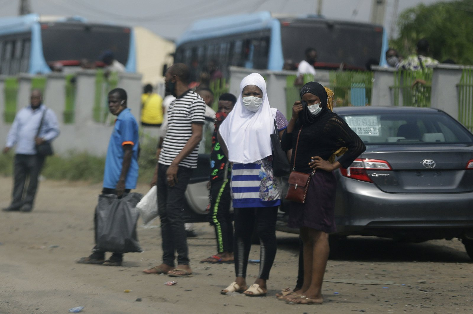 People wearing face masks to protect against the coronavirus wait for a commercial bus, Lagos, May 20, 2020. (AP Photo)