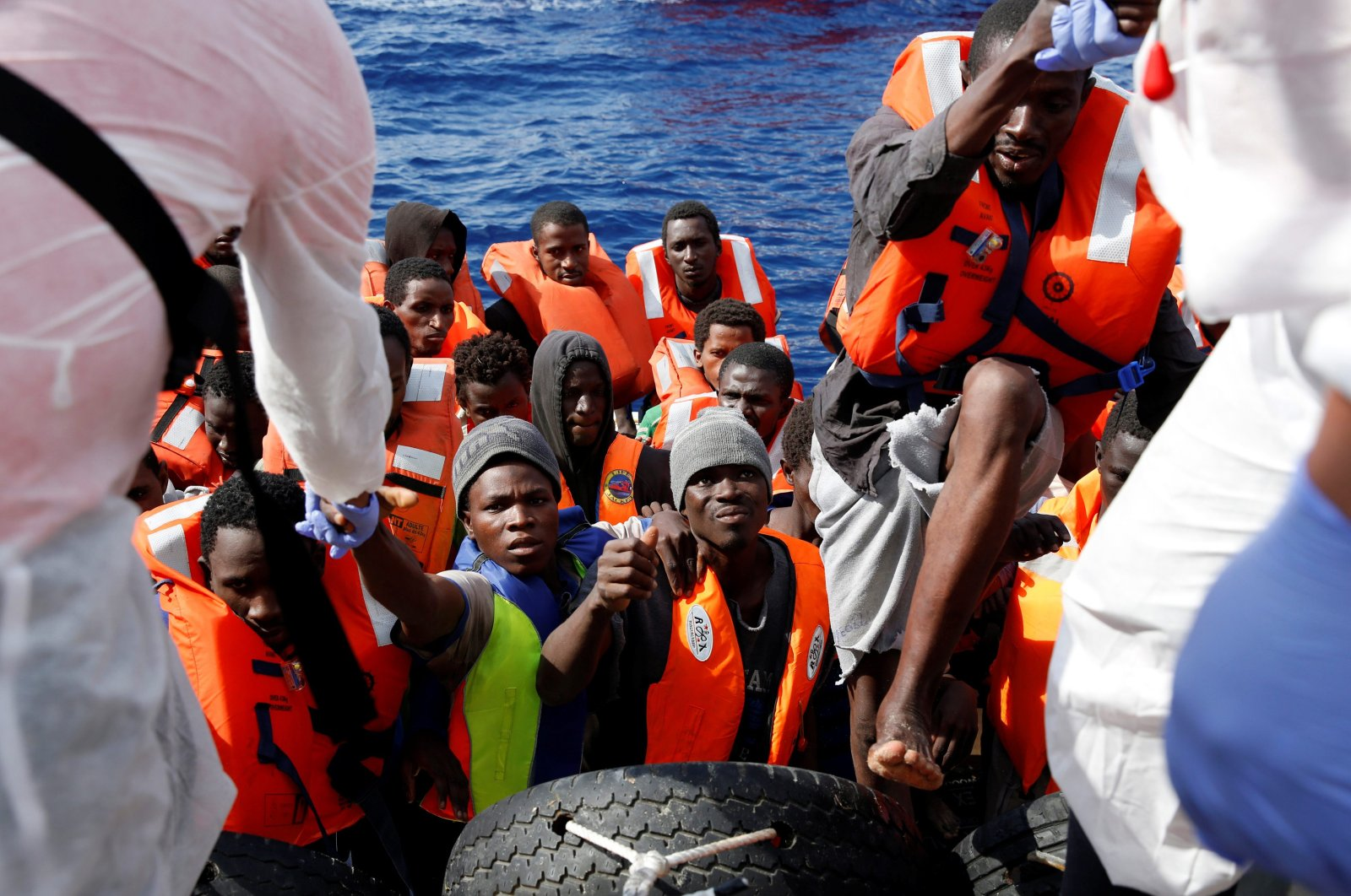 Migrants in a dinghy climb aboard the Migrant Offshore Aid Station (MOAS) ship Topaz Responder around 20 nautical miles off the coast of Libya, June 23, 2016. (Reuters Photo)