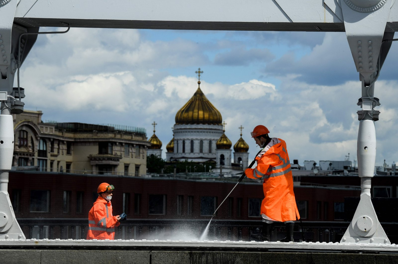 Municipal workers wearing face masks clean Krymsky Bridge across the Moskva river, with the Cathedral of Christ the Saviour seen in the background, in downtown Moscow on May 20, 2020. (AFP Photo)