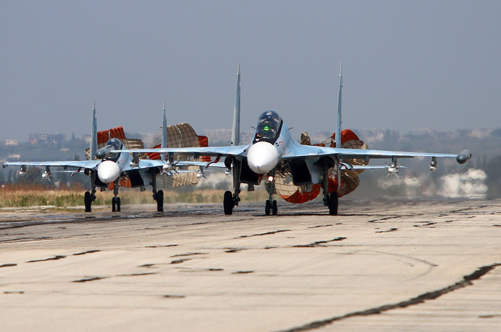 A picture taken on October 3, 2015 shows Russian Sukhoi SU-30 SM jet fighters landing on a runway at the Hmeimim airbase in the Syrian province of Latakia. (AFP Photo)