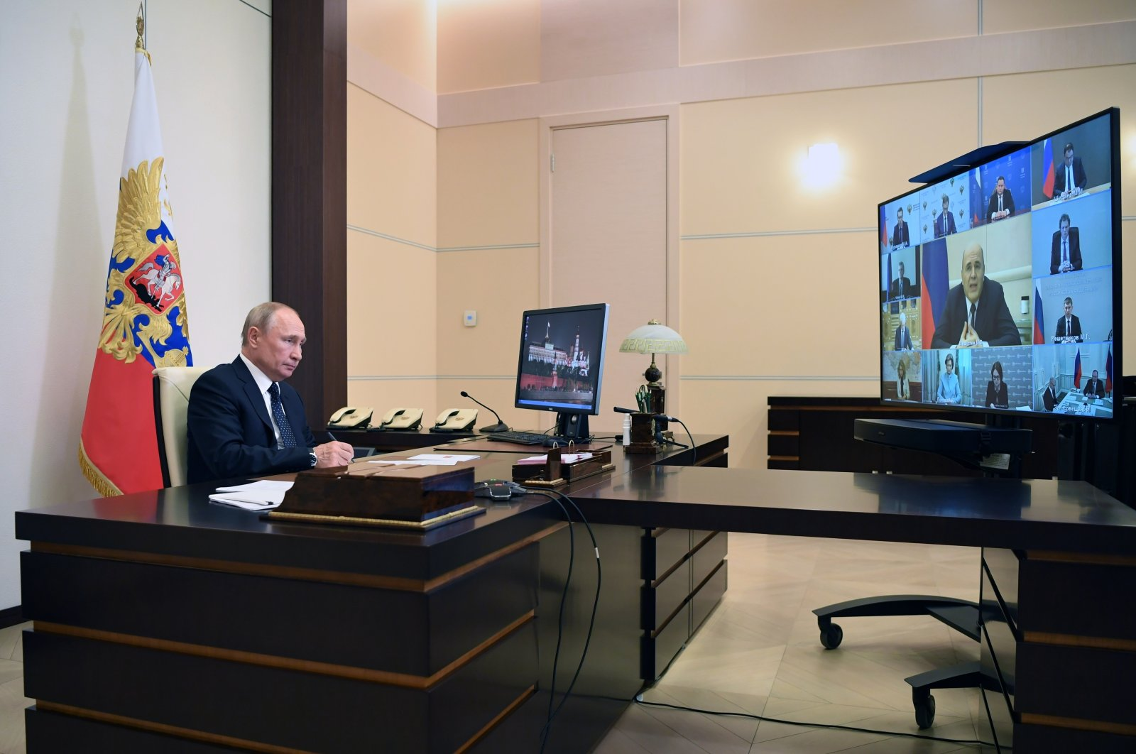 Russian President Vladimir Putin takes part in a videoconference with Cabinet officials, with Russian Prime Minister Mikhail Mishustin, who has fully resumed his duties after recovering from the coronavirus in the center of the screen, at the Novo-Ogaryovo residence outside Moscow, Russia, May 19, 2020. (Kremlin Pool Photo via AP Photo)