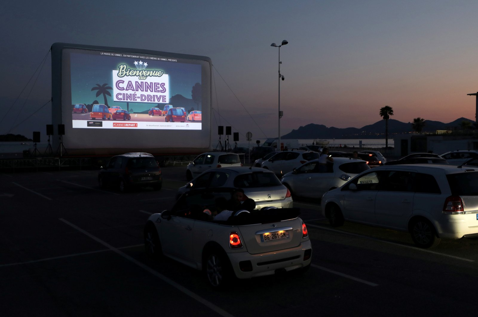 """People sit in their cars to watch the movie """"E.T. the Extra-Terrestrial"""" by Steven Spielberg at a drive-in cinema at la Pointe Croisette during the coronavirus outbreak, in Cannes, France, May 20, 2020. (REUTERS Photo)"""