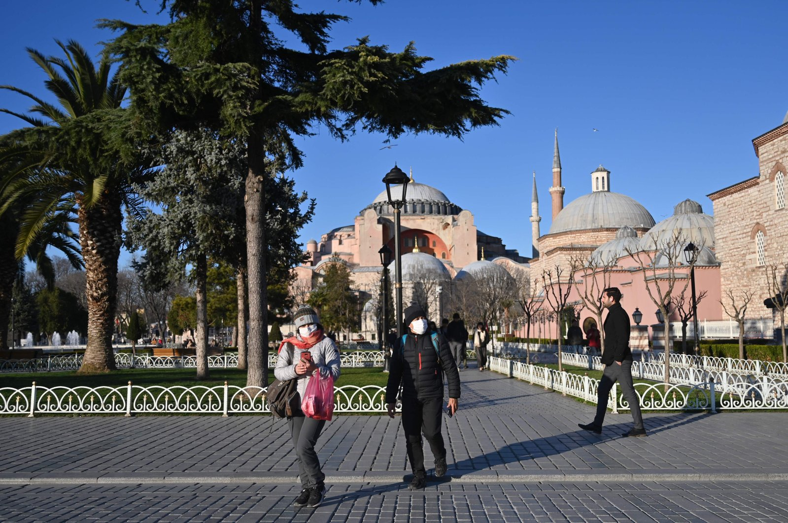 Tourists wear protective face masks as they walk near Hagia Sophia during the coronavirus outbreak, Istanbul, March 17, 2020. (AFP Photo)
