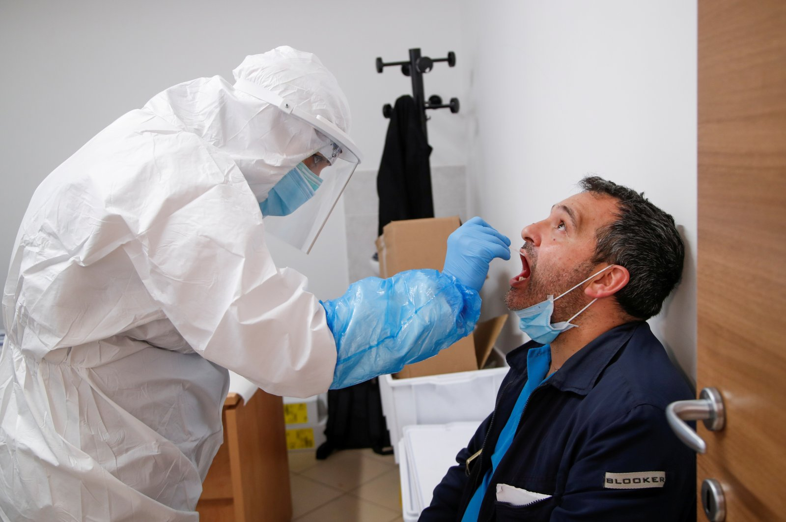 A health care worker takes a swab from a man in a medical center in Positano, Italy, May 22, 2020. (Reuters Photo)