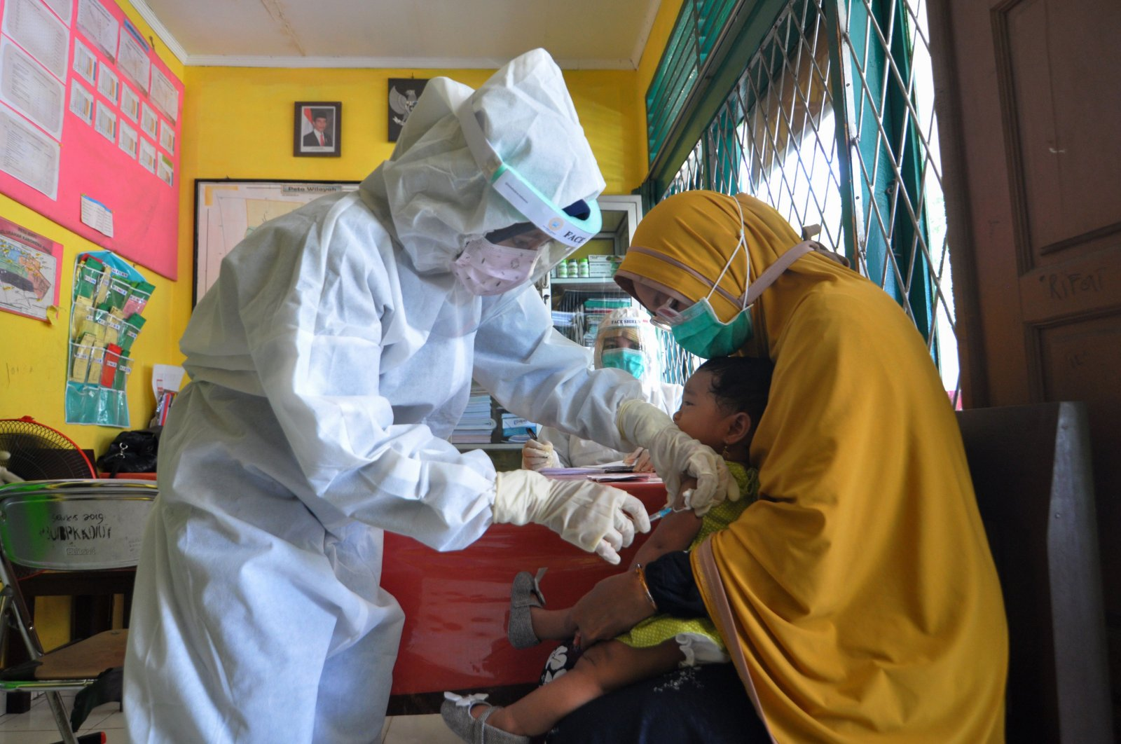 Nurses wearing protective gear give an injection of a vaccine for measles to a child at a health center in Palu, May 12, 2020. (AFP Photo)