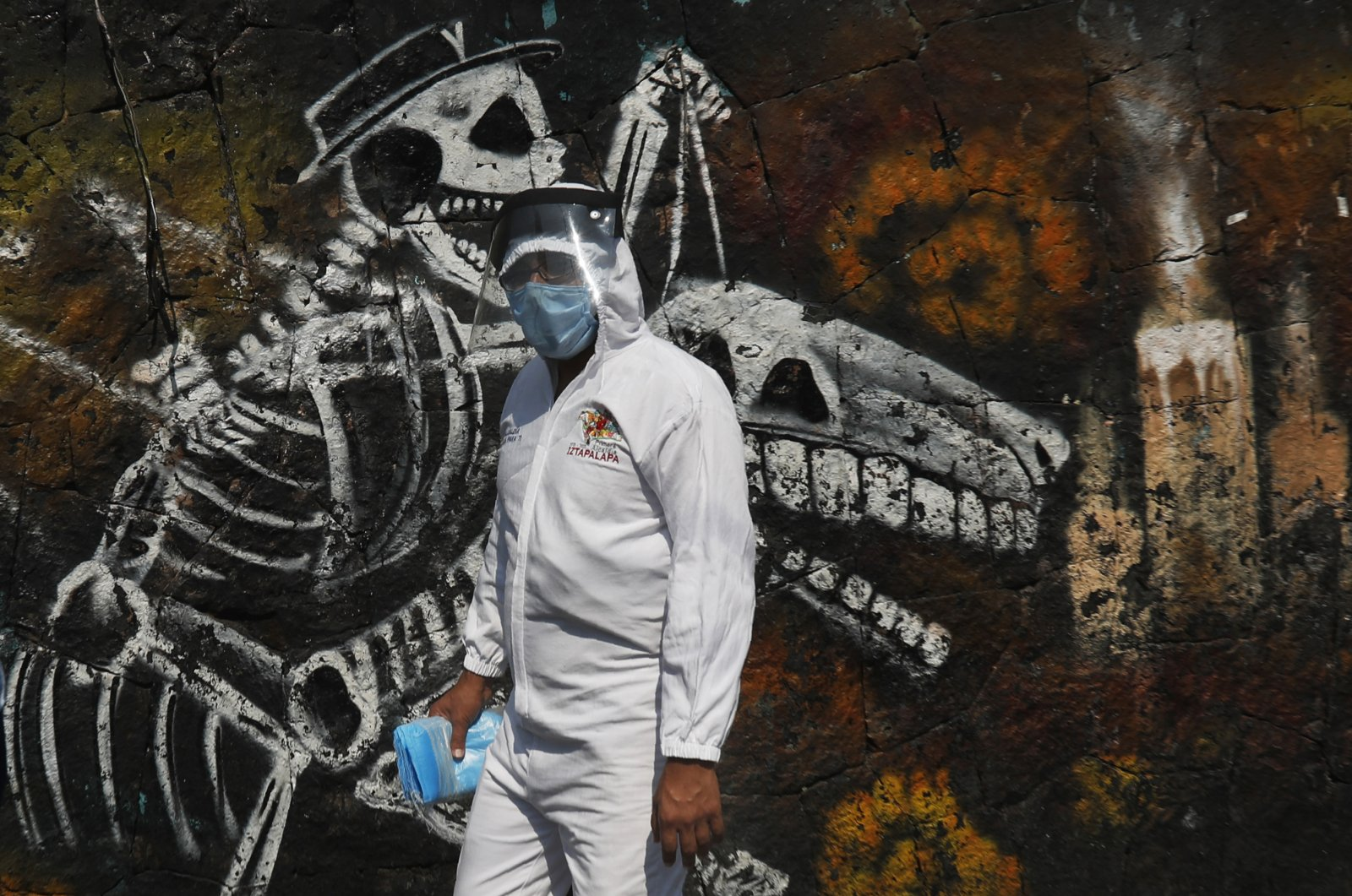 A municipal worker carries face masks to hand out at the San Nicolas Tolentino Pantheon that is making space for more burials amid the COVID-19 pandemic in the Iztapalapa area of Mexico City, Friday, May 22, 2020. (AP Photo)