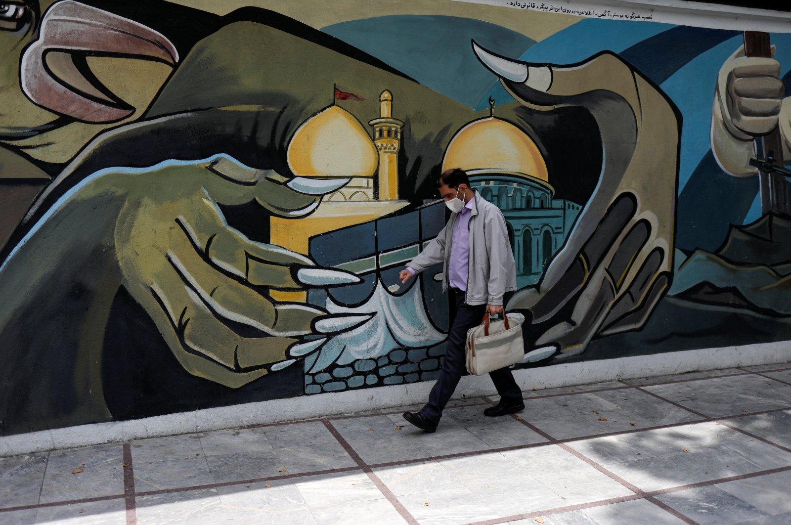 A man wearing a protective face mask walks past a Palestine mural on the wall following the outbreak of the coronavirus, Tehran, Iran, April 30, 2020. (WANA / Ali Khara via REUTERS)