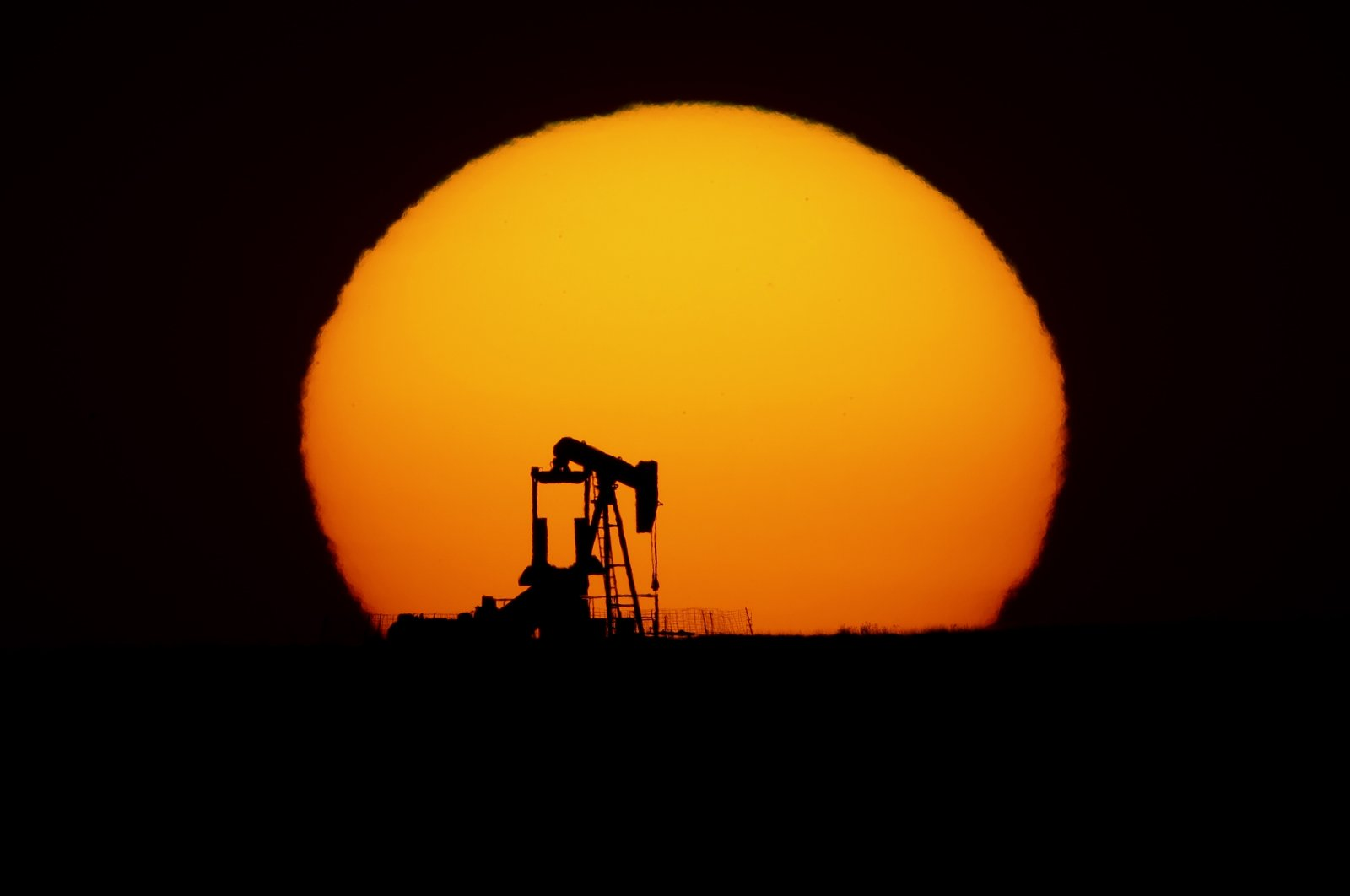 An idle oil pumping unit is silhouetted against the setting sun in a field south of Oakley, Kansas, U.S., May 20, 2020. (AP Photo)