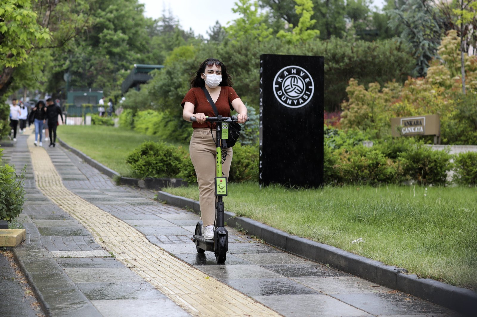 A woman wearing a face mask for protection against the new coronavirus, rides a scooter just hours before a four-day new curfew declared by the government in an attempt to control the spread of coronavirus, in Ankara, Turkey, Friday, May 22, 2020. (AP Photo)
