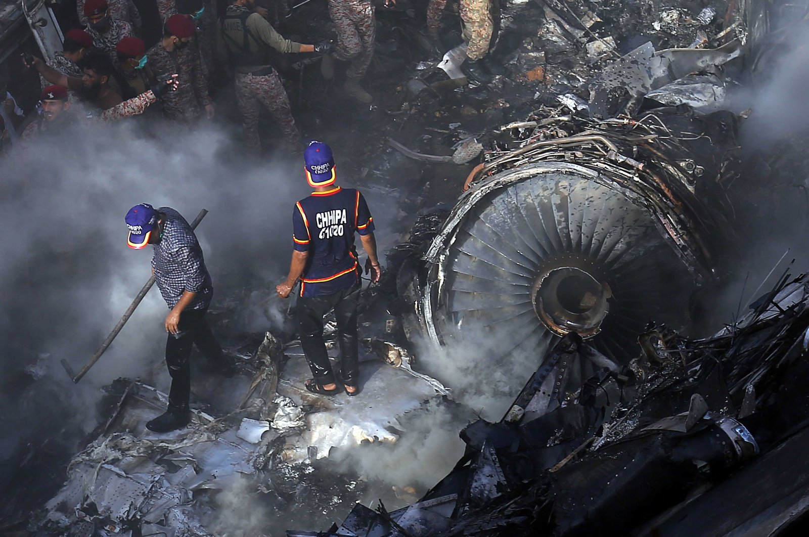 Rescue workers search for the bodies or survivors amid the wreckage of the passenger plane of state-run Pakistan International Airlines, after it crashed on a residential colony, in Karachi, Pakistan, 22 May 2020. (EPA)