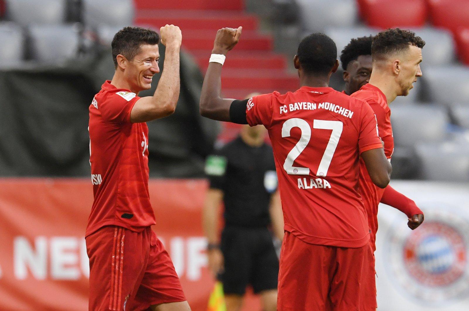 Bayern Munich's Polish forward Robert Lewandowski (L) celebrates scoring the third goal with Bayern Munich's Austrian defender David Alaba during their Bundesliga match against Eintracht Frankfurt, Munich, southern Germany, May 23, 2020.