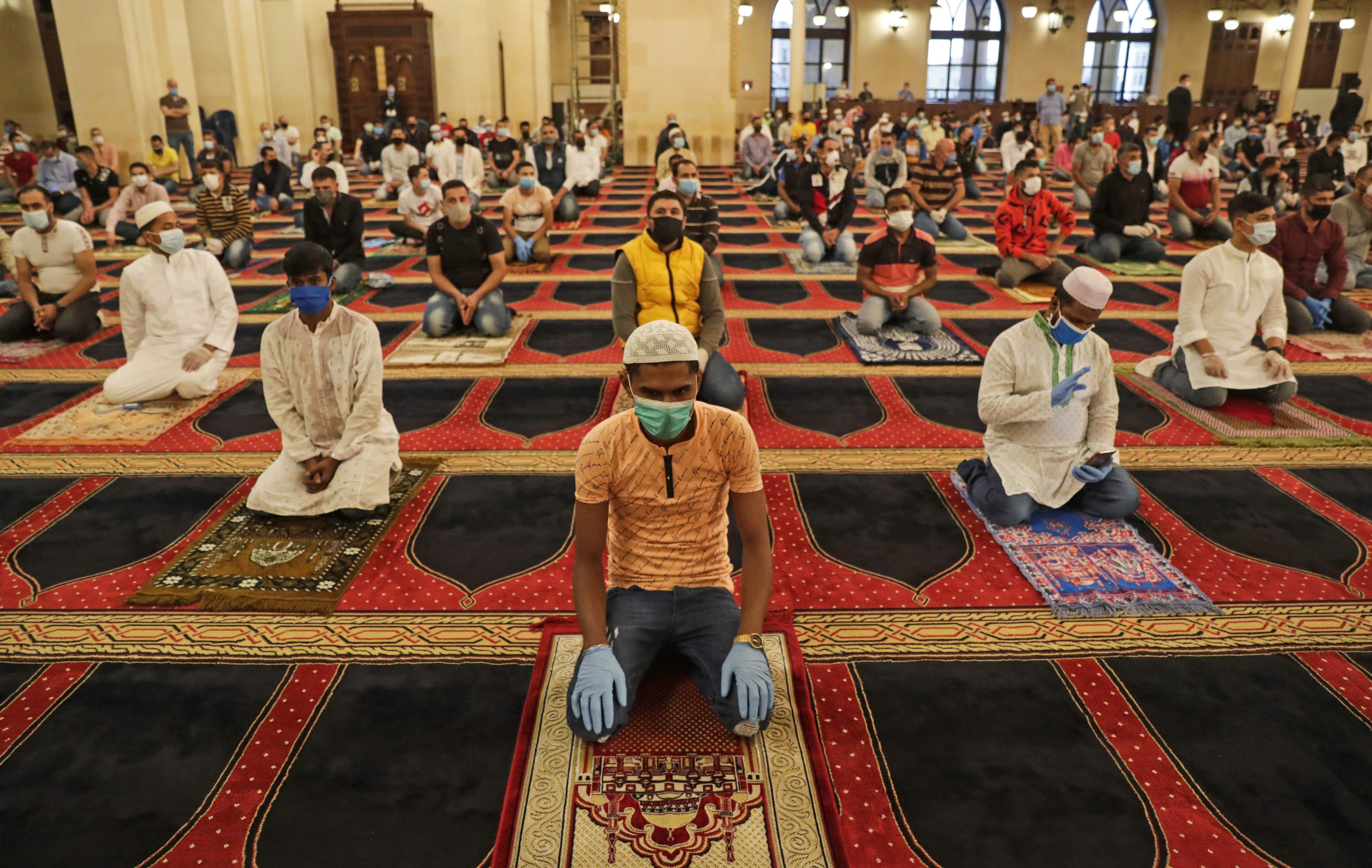 Muslims worshippers take part in a morning prayer to celebrate the Eid al-Fitr holiday while wearing protective masks and maintaining social distancing due to the COVID-19 pandemic, at Mohammed al-Amin Mosque, Beirut, Lebanon, May 24, 2020. (AFP Photo)