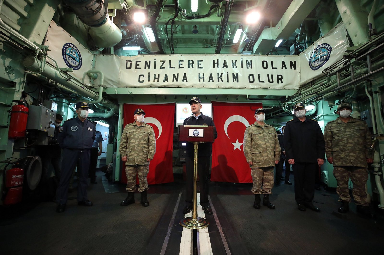 """National Defense Minister Hulusi Akar during a speech aboard TCG Barbaros vessel on May 24, 2020 with the slogan on the background reading """"One who dominates the seas, dominates the world"""" (DHA Photo)"""