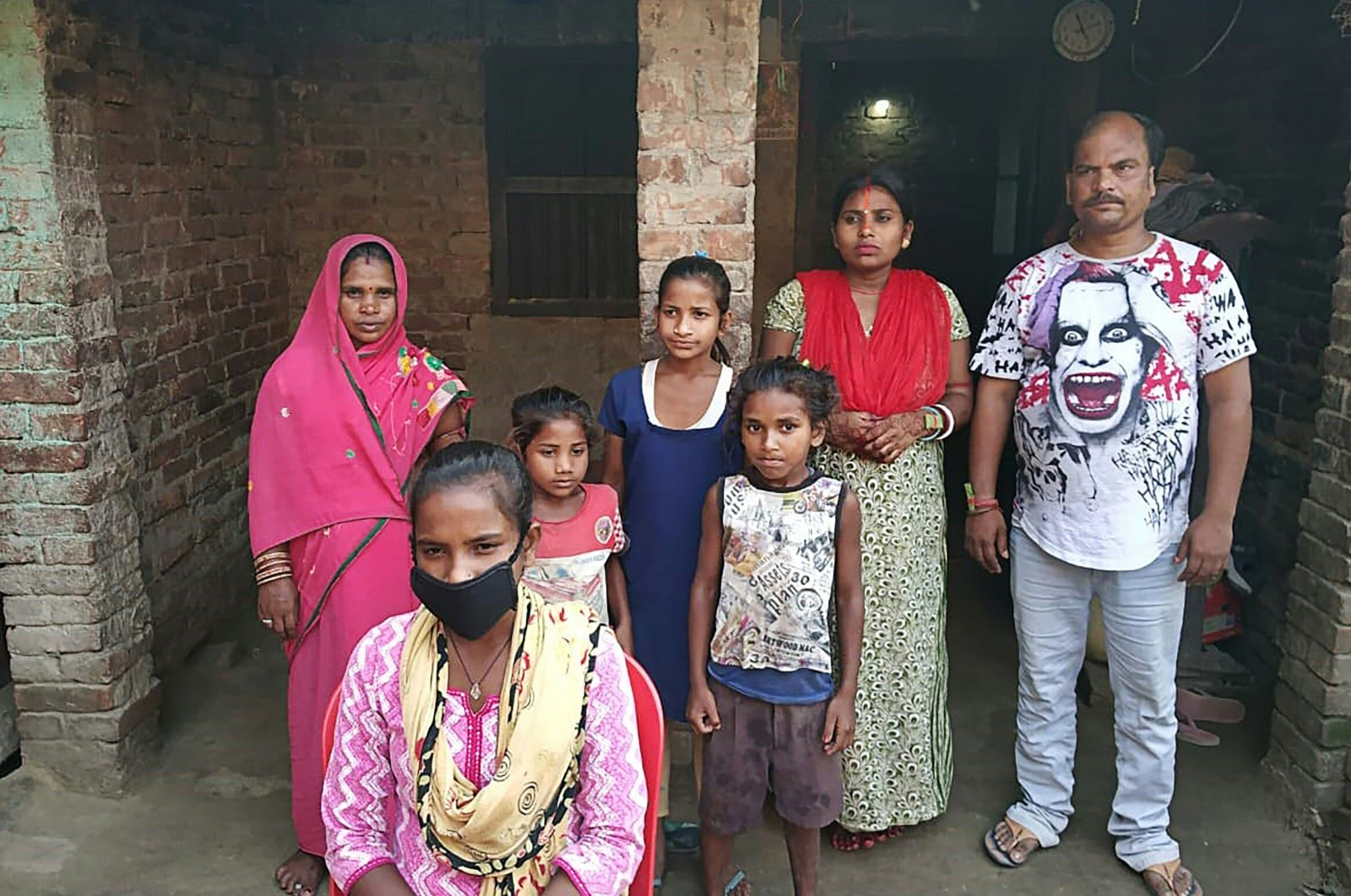 Jyoti Kumari Paswan, 15, (C-bottom) and her family stand in front of their house in Siruhully village, the Darbhanga district, India, May 23, 2020. (Photo by STR / AFP)