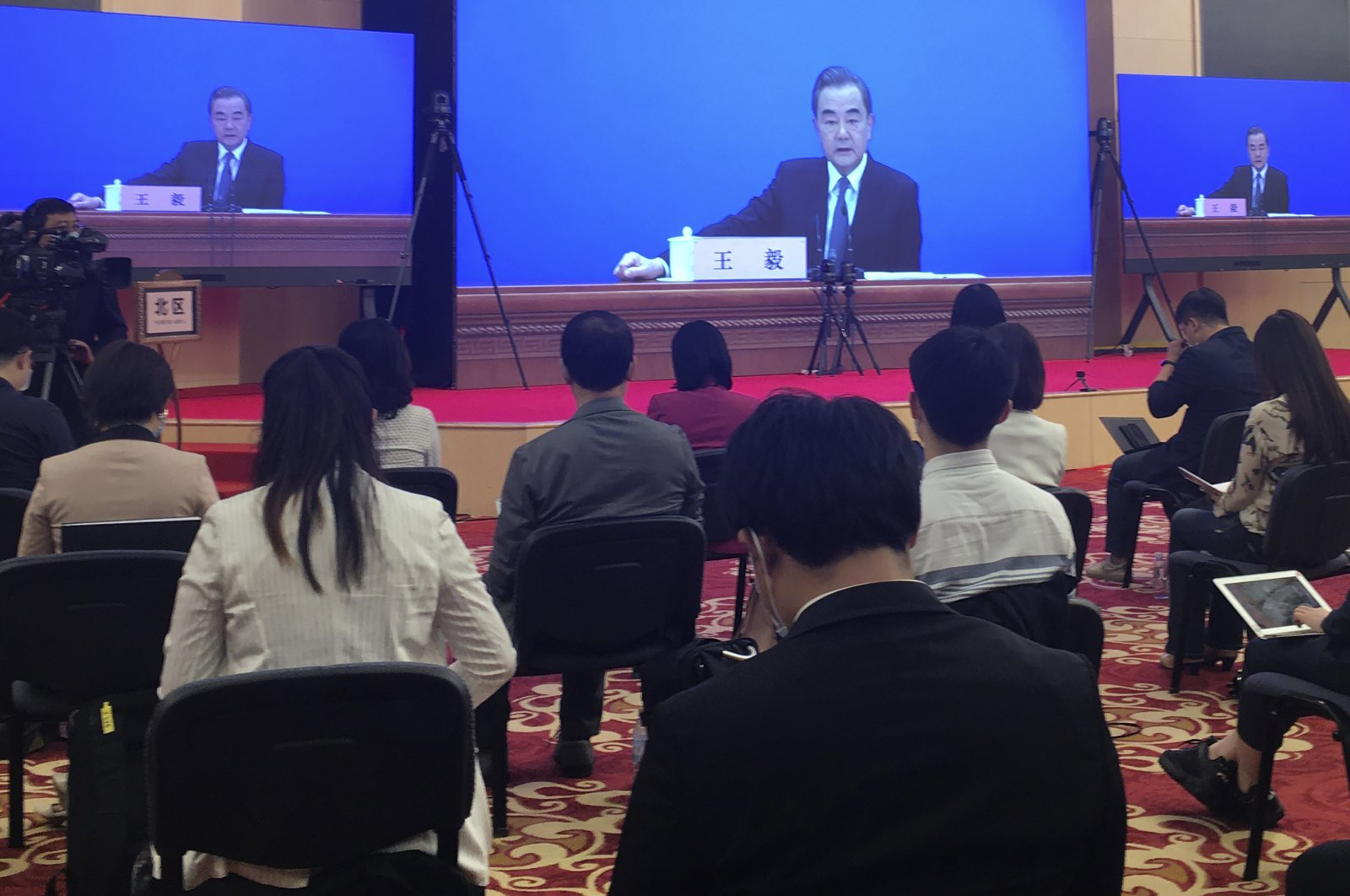 China's Foreign Minister Wang Yi is broadcast remotely on big screens during a press conference on the sideline of the National People's Congress, Beijing, May 24, 2020. (AP Photo/Ken Moritsugu)