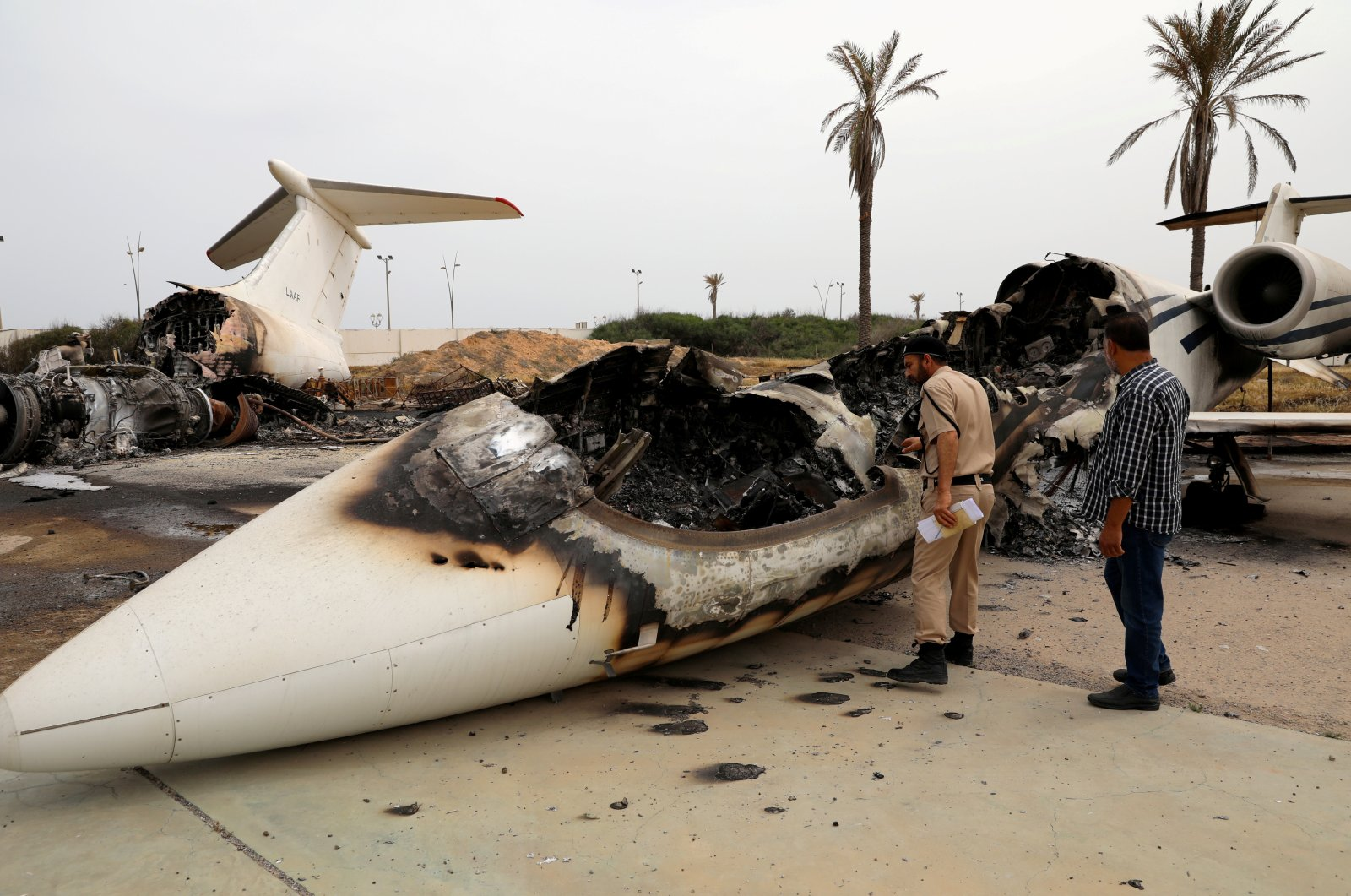 A policeman and a man inspect a passenger plane damaged by shelling at Mitiga airport in Tripoli, Libya, May 10, 2020. (Reuters Photo)
