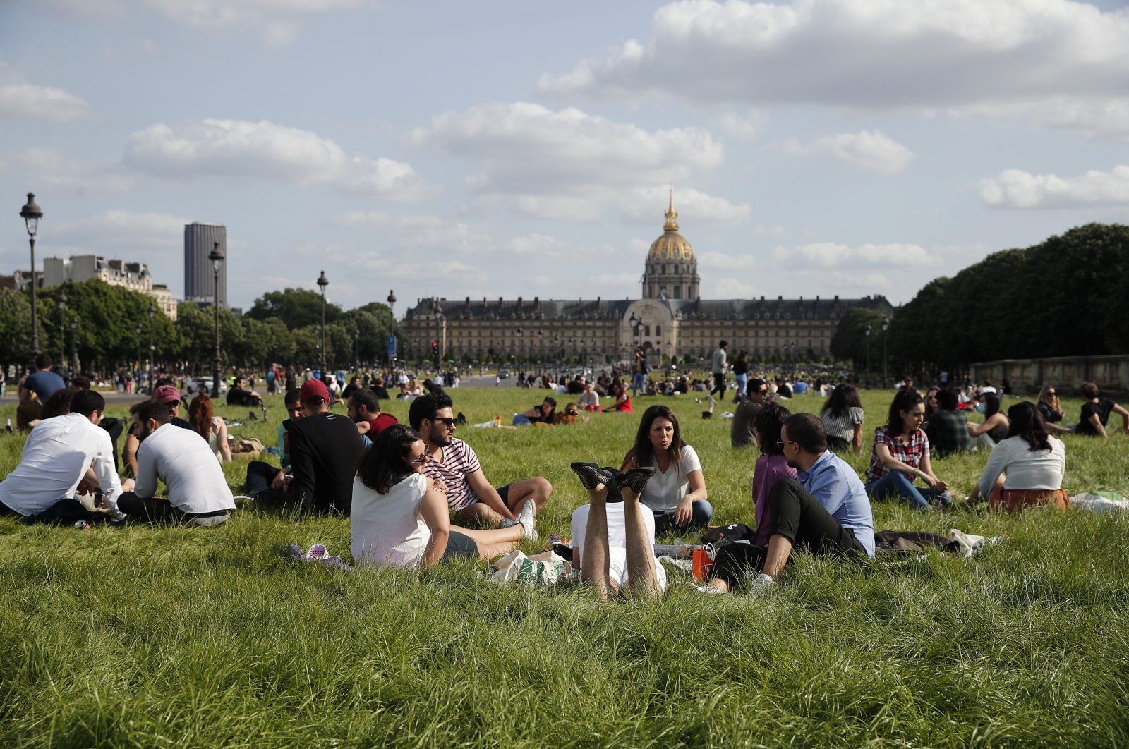 Parisians relax in the non-mowed lawn next to the Invalides Museum in Paris, Sunday, May 24, 2020 as France gradually lifts its COVID-19 lockdown. (AP Photo)
