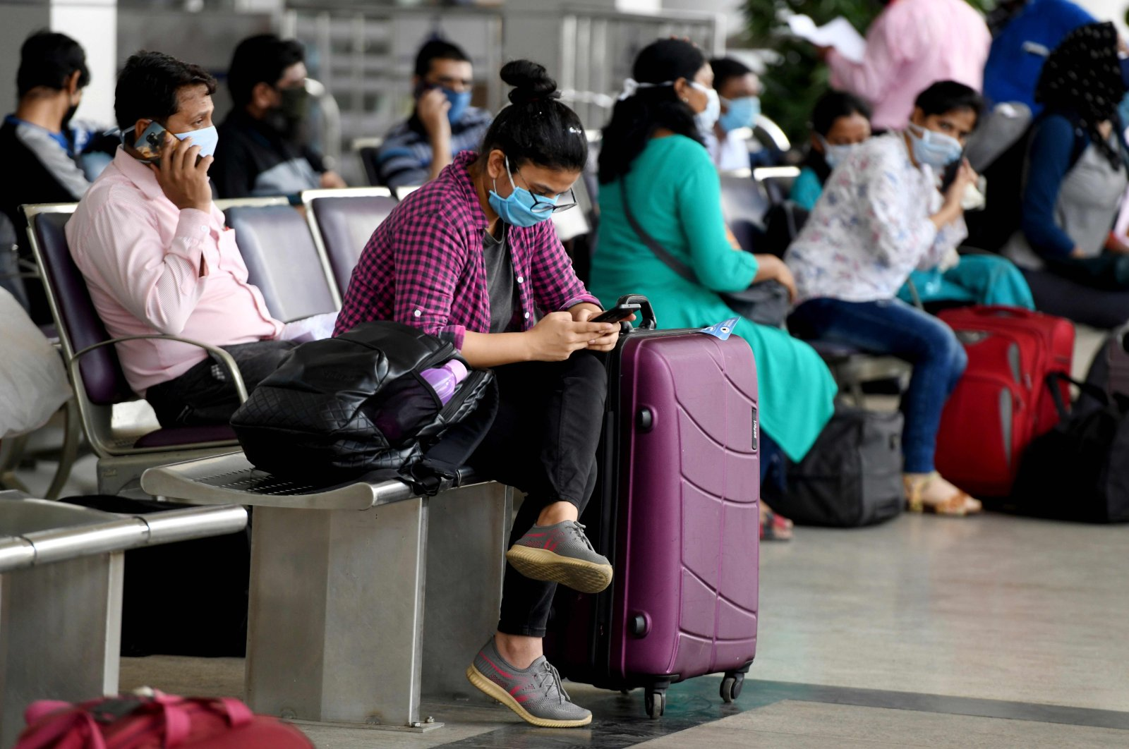 A passenger checks her mobile phone as she waits to check in at Kamaraj Domestic Airport during the first day of the resumption of domestic flights after the government imposed a nationwide lockdown as a preventive measure against the spread of the coronavirus, Chennai, May 25, 2020. (AFP Photo)