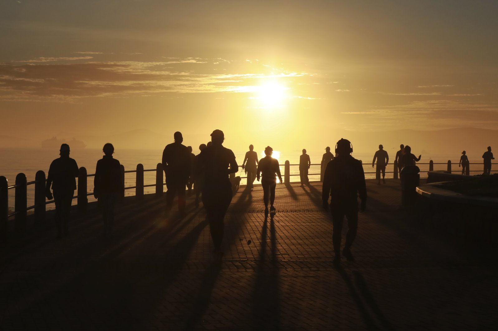 In this file photo taken Monday May 18, 2020, people exercise along the promenade at sunrise in Sea Point, Cape Town, South Africa, as the country marked day 53 of a strict government lockdown in a bid to prevent the spread of coronavirus. (AP Photo)
