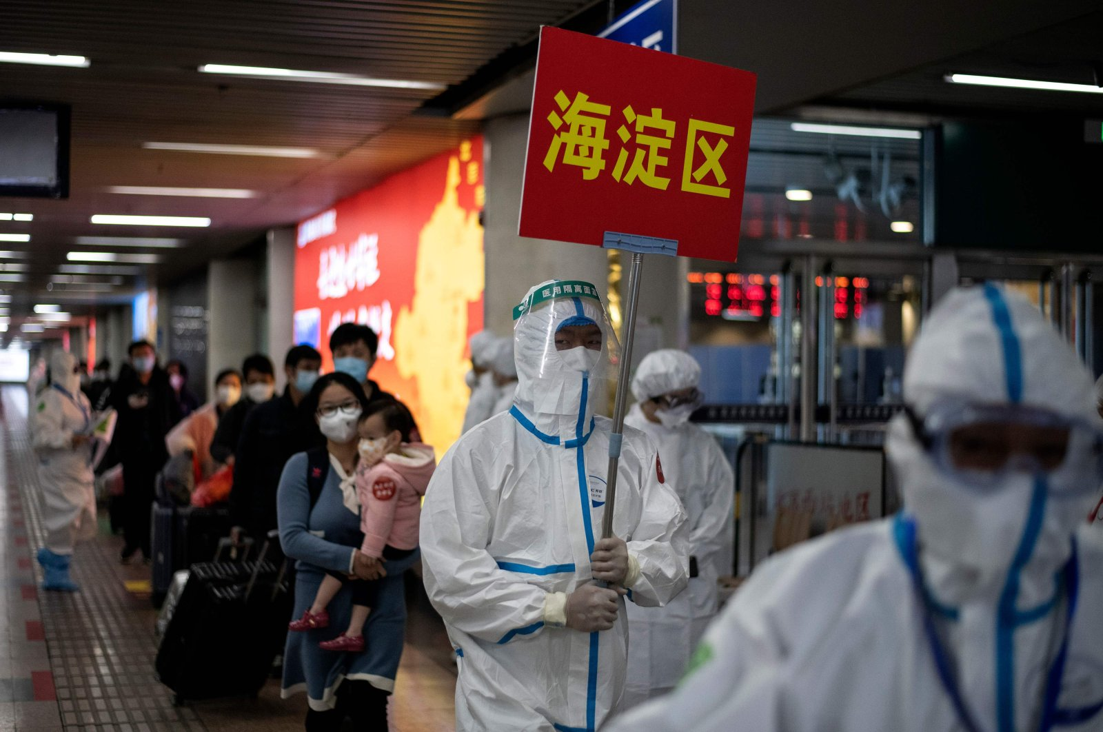 Transport personnel wearing hazmat suits guide travelers arriving from Wuhan to buses, which will take them to their quarantine locations, at Beijing West Railway Station, April 15, 2020. (AFP Photo)