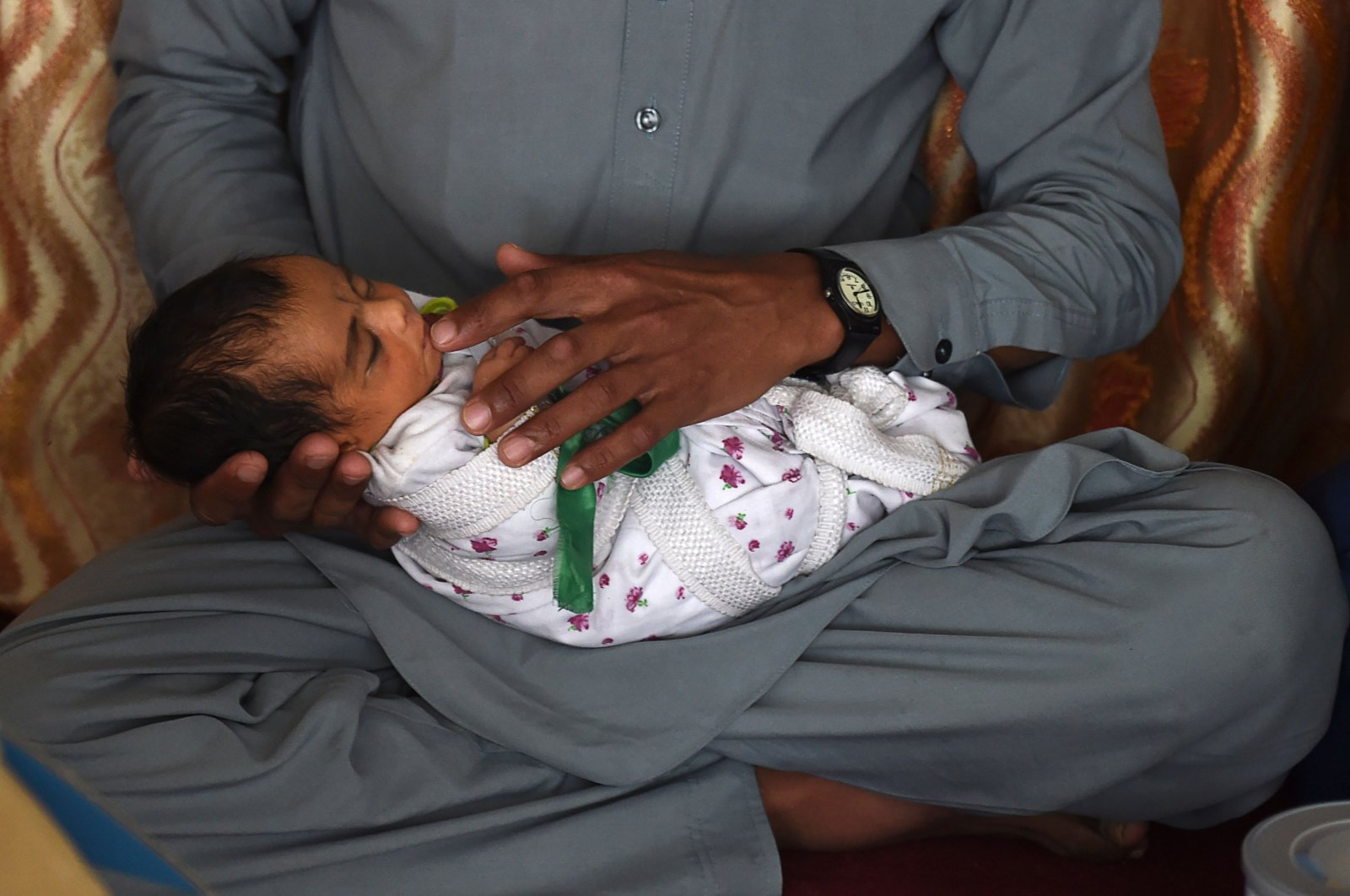 Hasan Ali, 32, and his newborn daughter, Roya, survivors of an attack by militants on a maternity ward in Kabul, sit in their home after receiving relief aid from a charity on the outskirts of the capital city, Kabul, May 22, 2020. (AFP Photo)