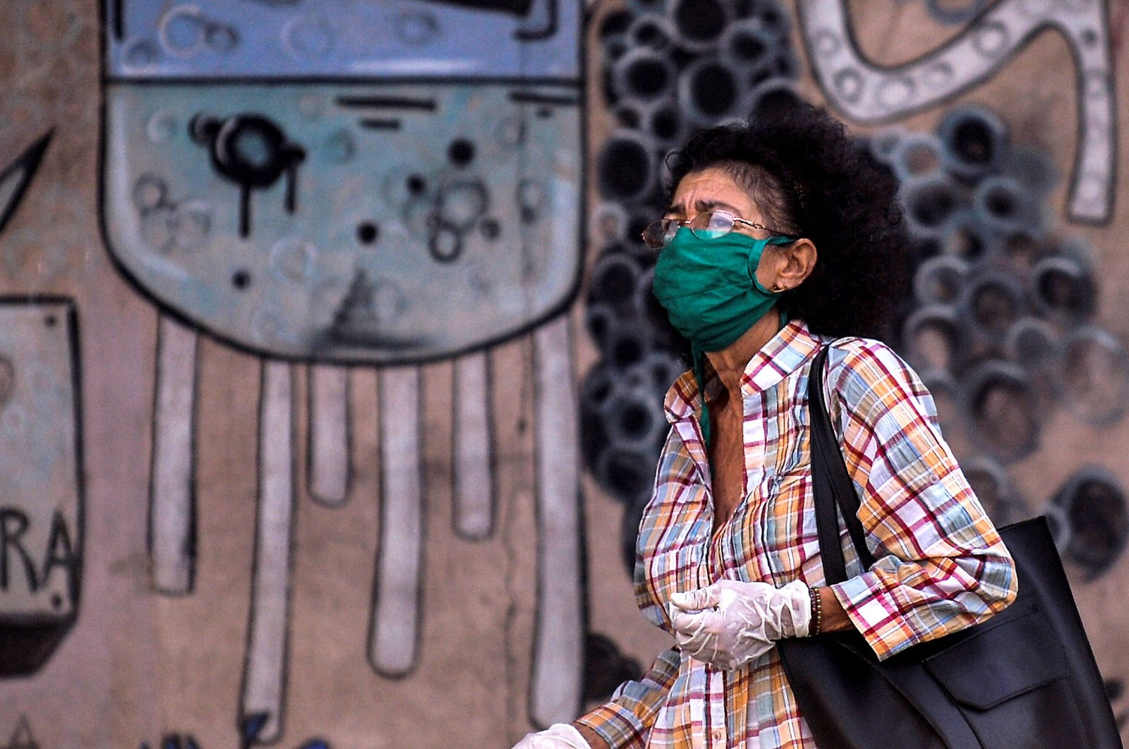 A woman wearing a face mask and gloves walks along a street in Havana, Cuba, May 25, 2020. (AFP Photo)