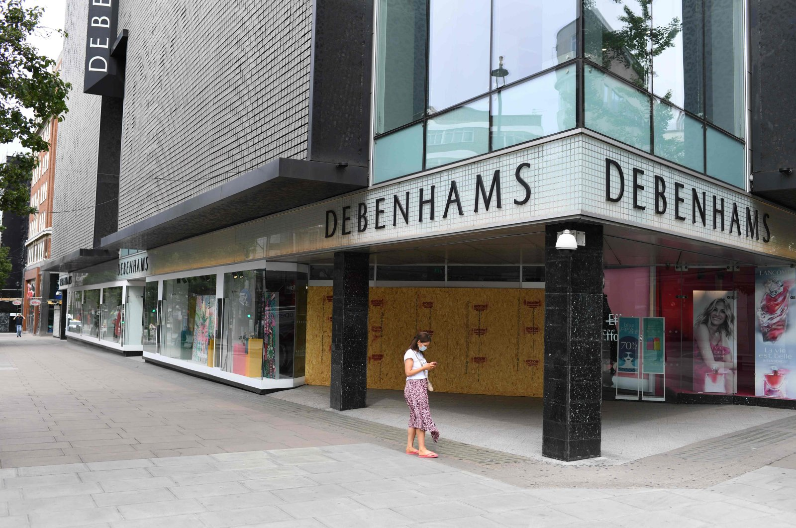 A woman wearing a face mask as a precaution walks past the shut and boarded up Debenhams department store on Oxford Street, London, U.K., May 22, 2020. (AFP Photo)
