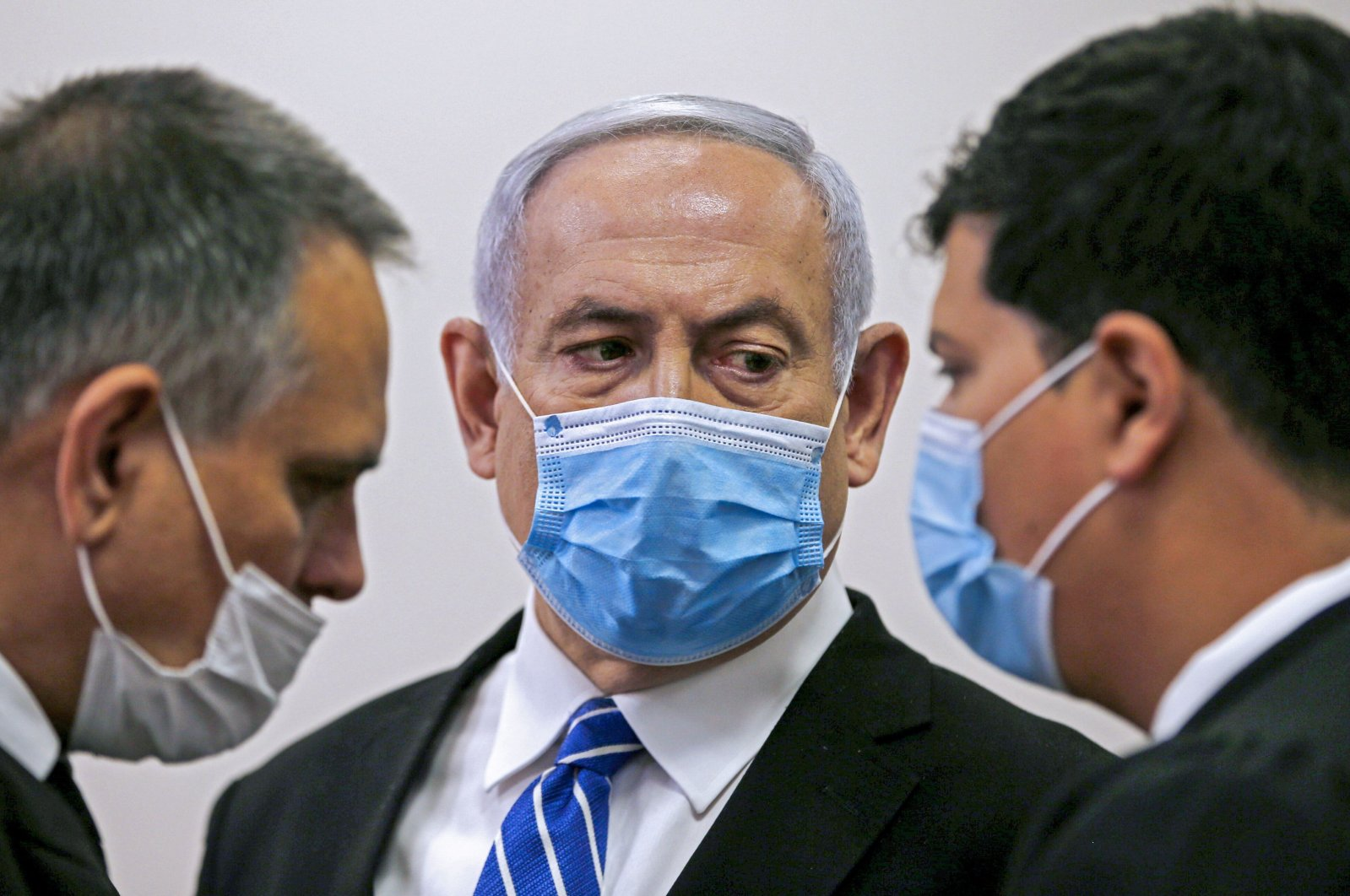 Israeli Prime Minister Benjamin Netanyahu (C), wearing a protective face mask, speaks with his lawyer inside a courtroom during the first day of his corruption trial, Jerusalem, May 24, 2020.  (AFP Photo)