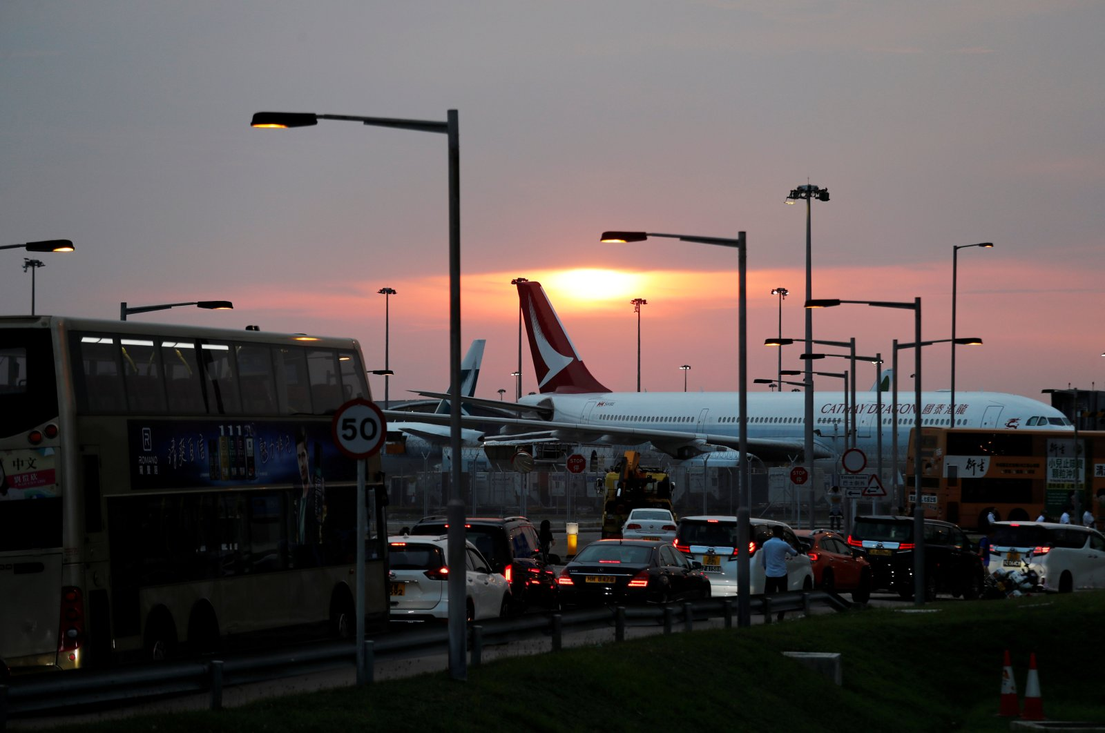 A picture shows a traffic jam along a highway as a Cathay Dragon plane is pictured in the background during an anti-extradition bill demonstration after a woman was shot in the eye in a protest in Hong Kong International Airport, Hong Kong, Aug. 12, 2019. (Reuters Photo)