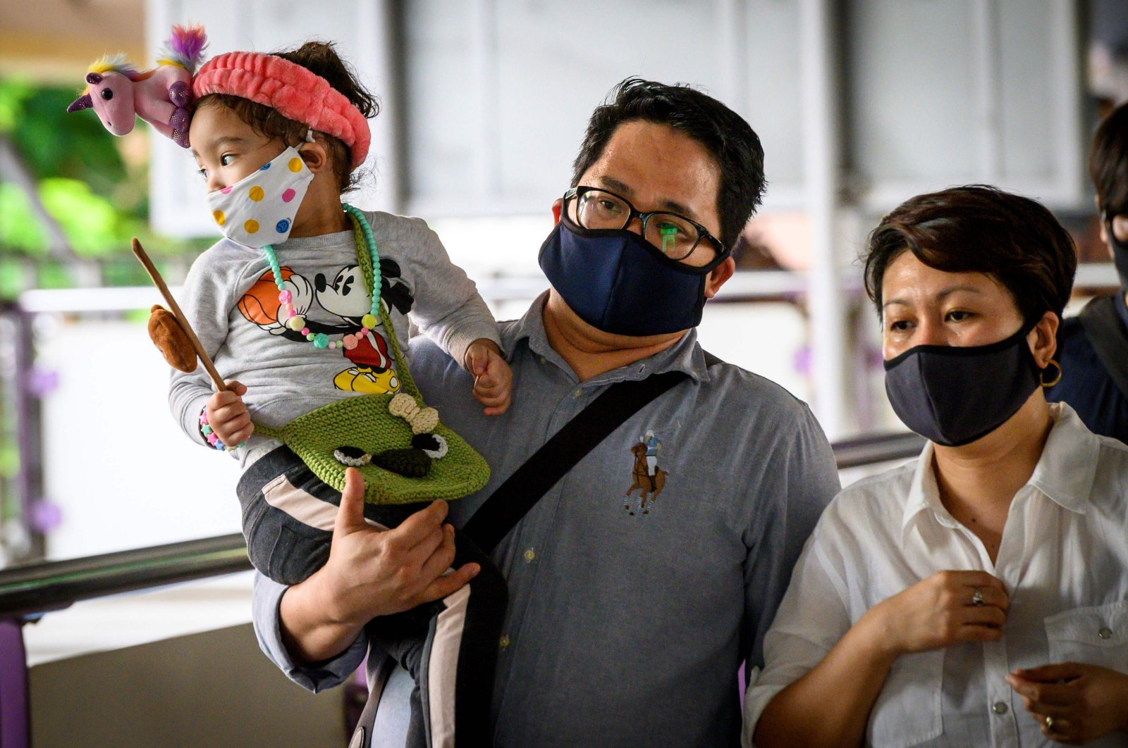 A child wearing a face mask is carried into a train station at rush hour in Bangkok, Thailand, as Thais continued their return to work following the lifting of restrictions to halt the spread of the coronavirus, May 25, 2020. (AFP Photo)