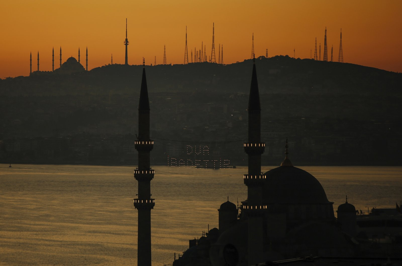 """Istanbul's historic Süleymaniye Mosque seen with a traditional roof ridge reading """"Prayer is worship"""" and the Bosporus seen at dusk, May 24, 2020. (AP Photo)"""