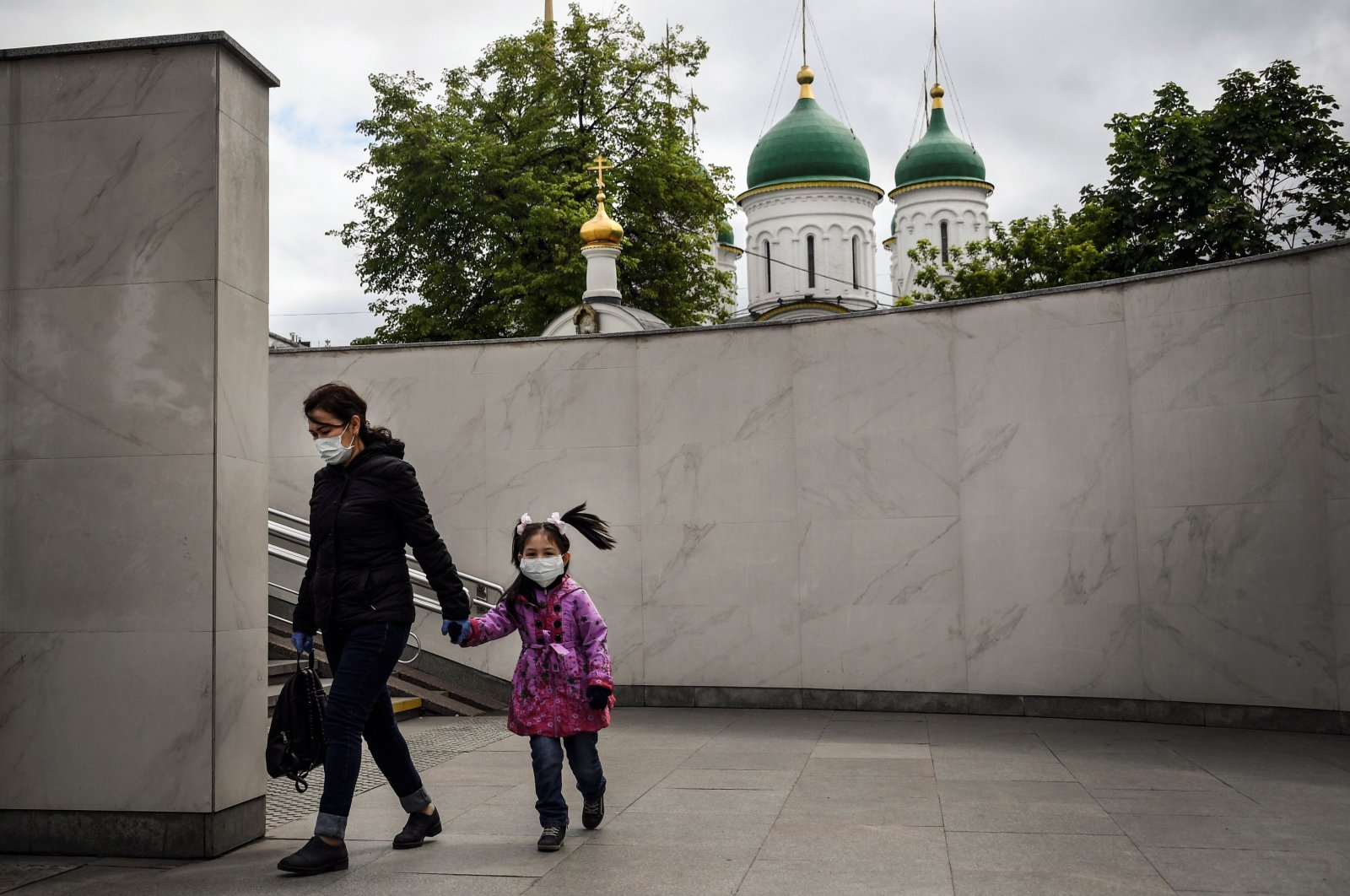 A woman and a girl wearing protective face masks walk through a pedestrian underpass, Moscow, Russia, May 22, 2020. (AFP Photo)