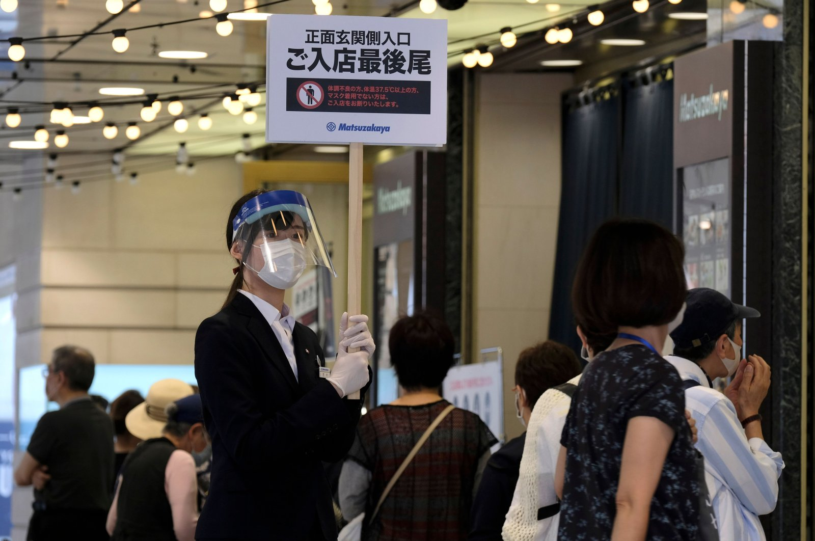An employee wearing a face shield amid concerns of the COVID-19 coronavirus holds up a sign as people wait in a queue to visit Ueno's Matsuzakaya department store in Tokyo on May 26, 2020. (AFP Photo)