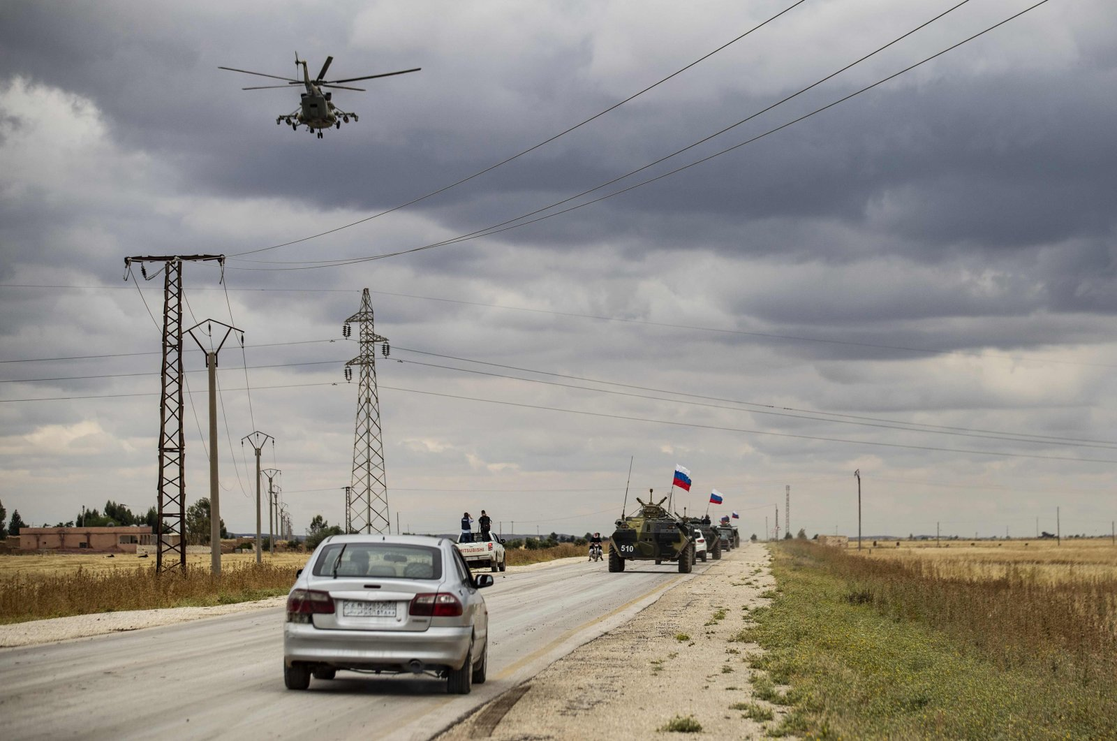 A Russian military helicopter accompanies military and civilian vehicles along the M4 highway by the town of Tal Tamr on May 25, 2020. (AFP Photo)