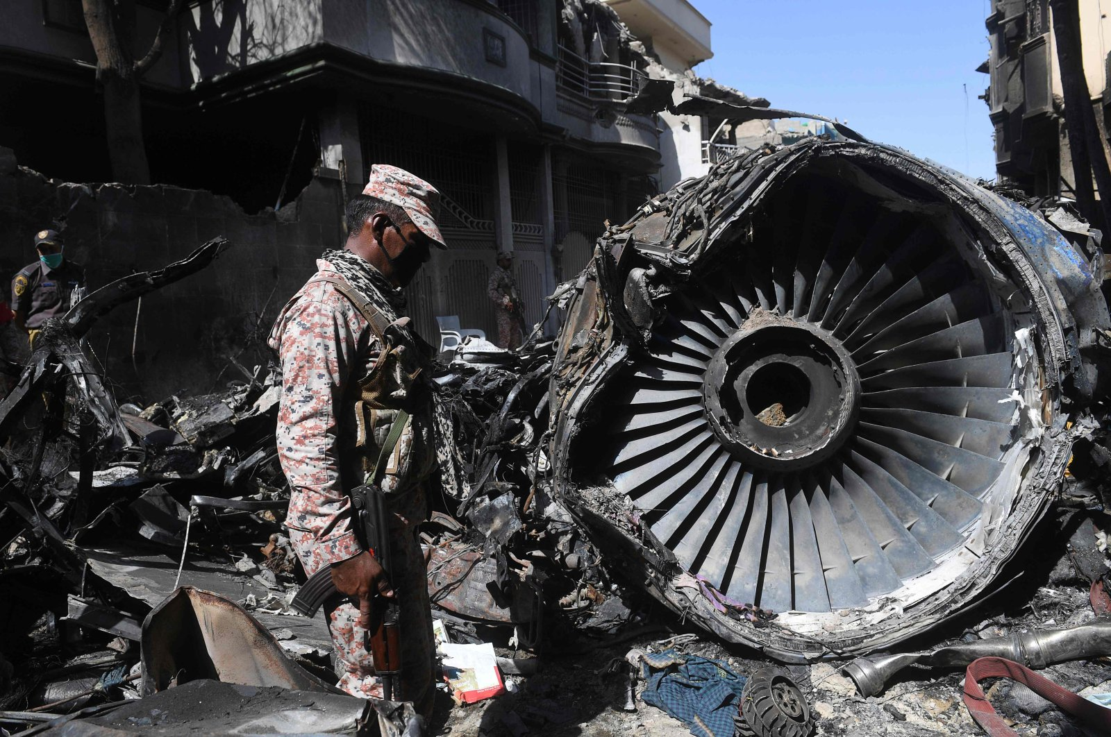 Security personnel stand beside the wreckage of a plane at the site after a Pakistan International Airlines aircraft crashed in a residential area in Karachi, on May 24, 2020. (AFP Photo)