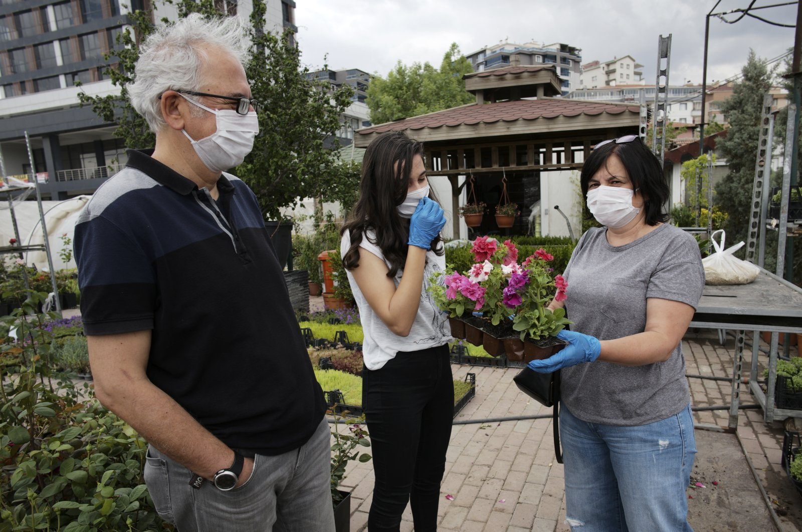 A family wearing protective face masks buy flowers just hours before a four-day curfew came into effect in Ankara, Turkey, Friday, May 22, 2020. (AP Photo)