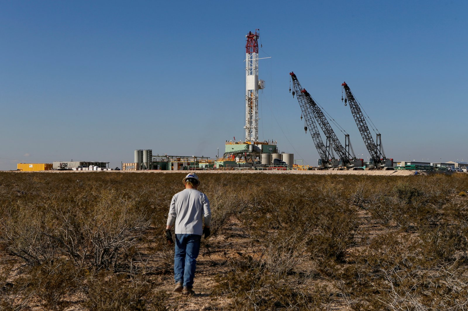 An oil worker walks toward a drill rig after placing ground monitoring equipment in the vicinity of the underground horizontal drill in Loving County, Texas, U.S., Nov. 22, 2019. (Reuters Photo)