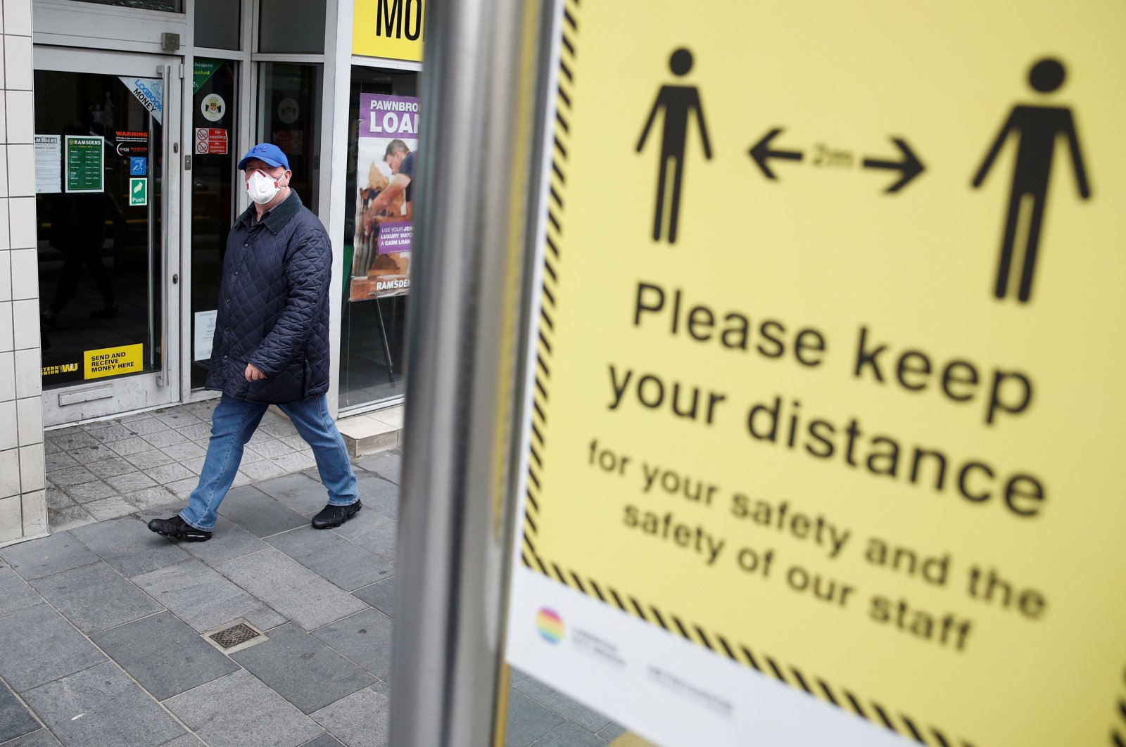 A man wearing a face mask walks by a social distance sign in Liverpool, following the outbreak of the coronavirus disease (COVID-19), Liverpool, Britain, May 26, 2020. (Reuters Photo)