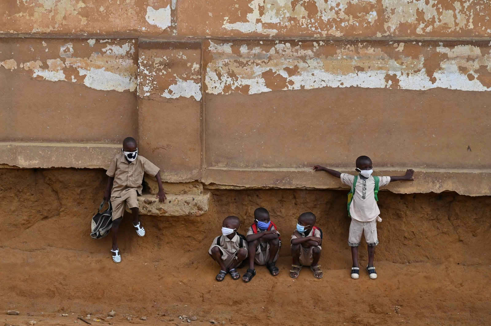 School children wearing face masks sit outside their classroom at a primary school, Attecoube, Ivory Coast, May 25, 2020. (AFP Photo)